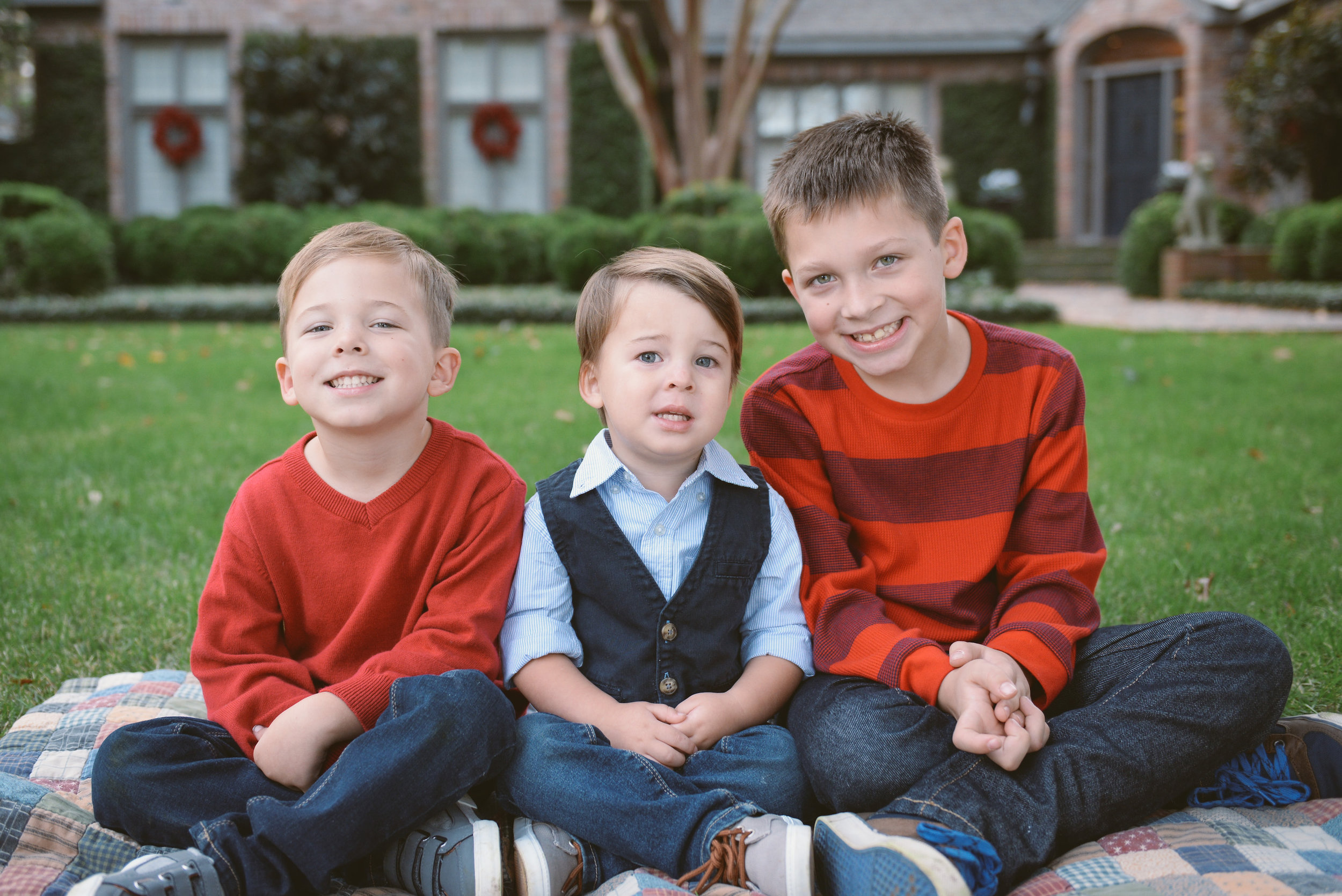 three brothers sitting on grass