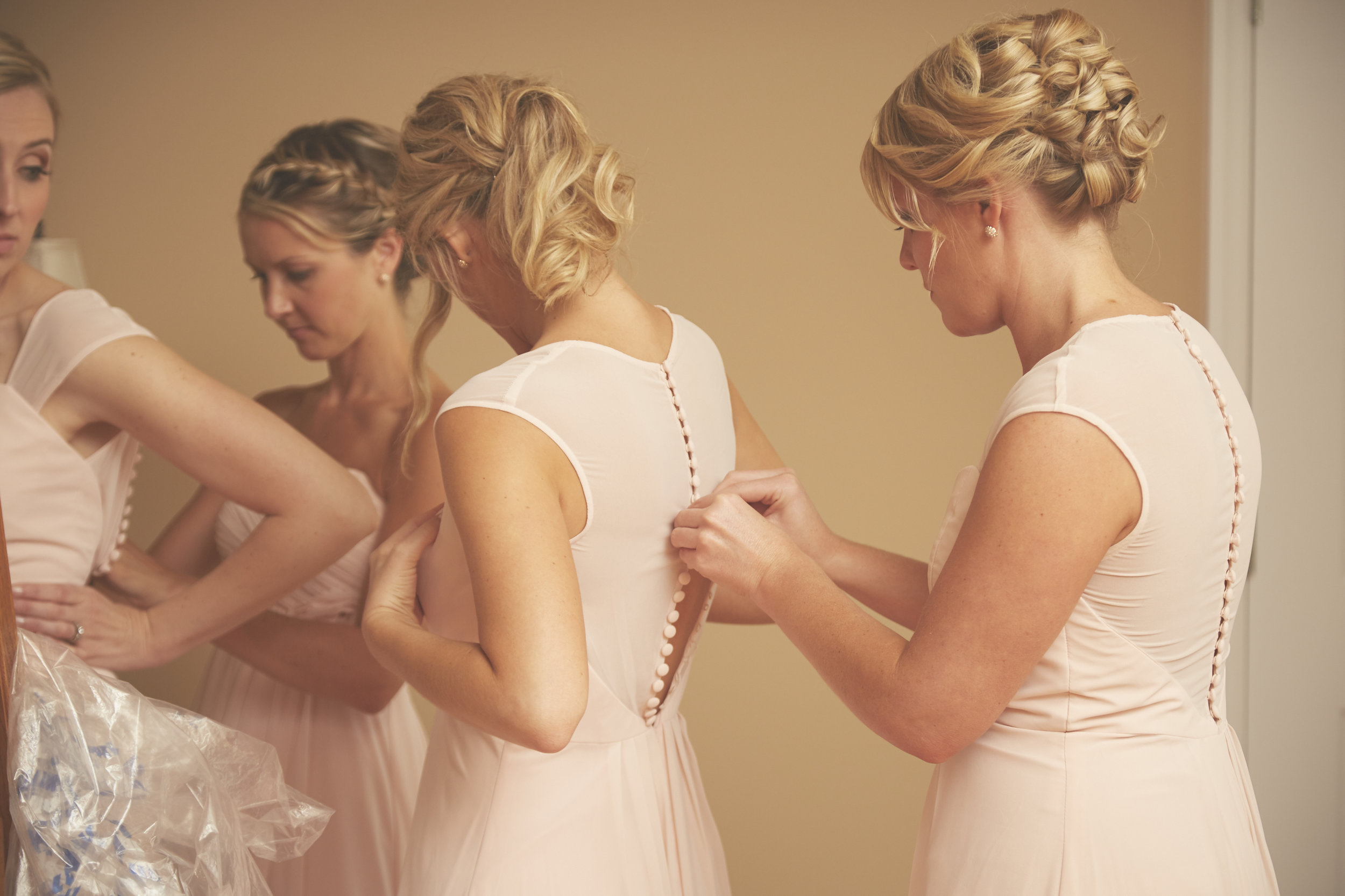 bridesmaids in pink dresses getting ready