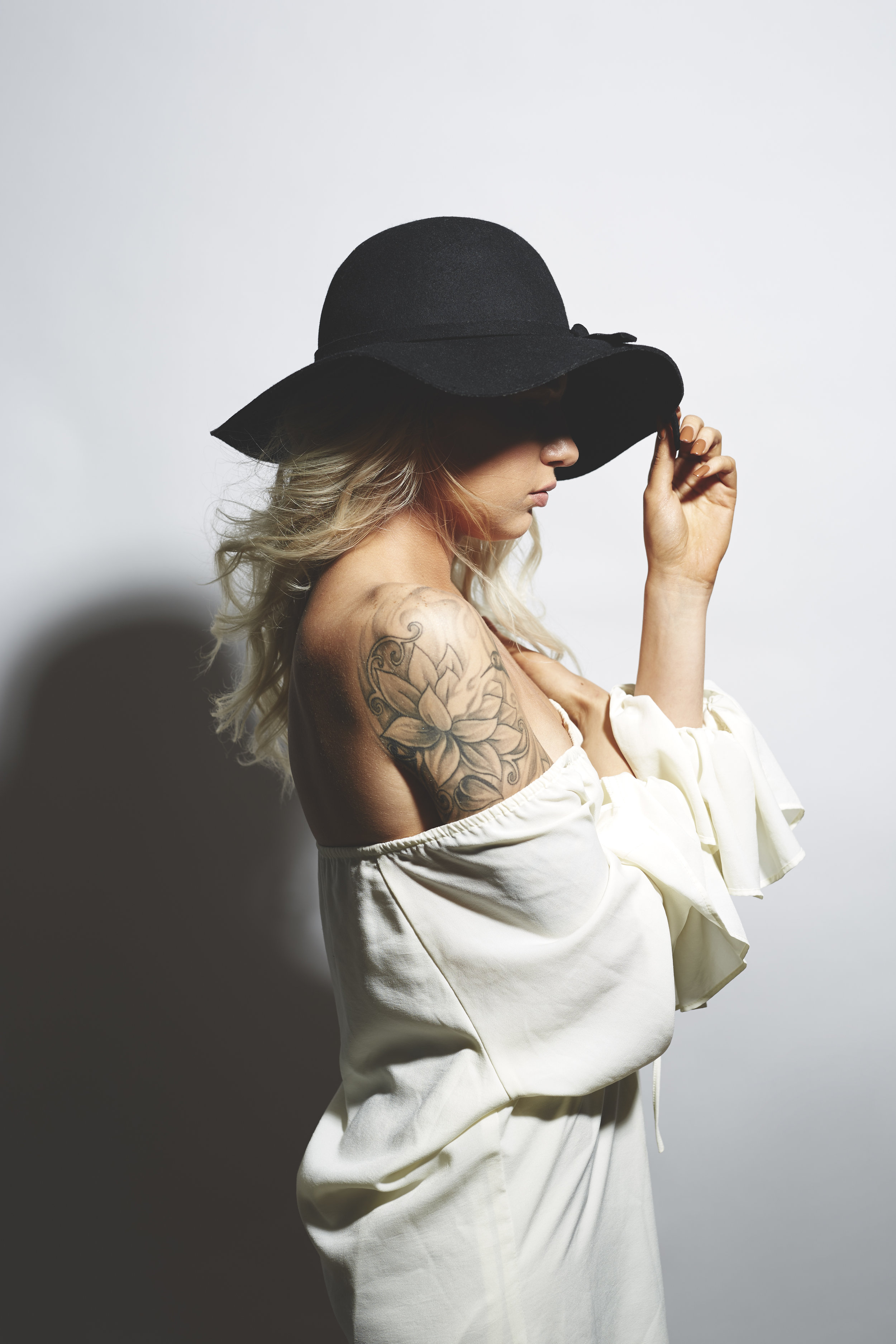 studio lights on model in sunhat with tattoos