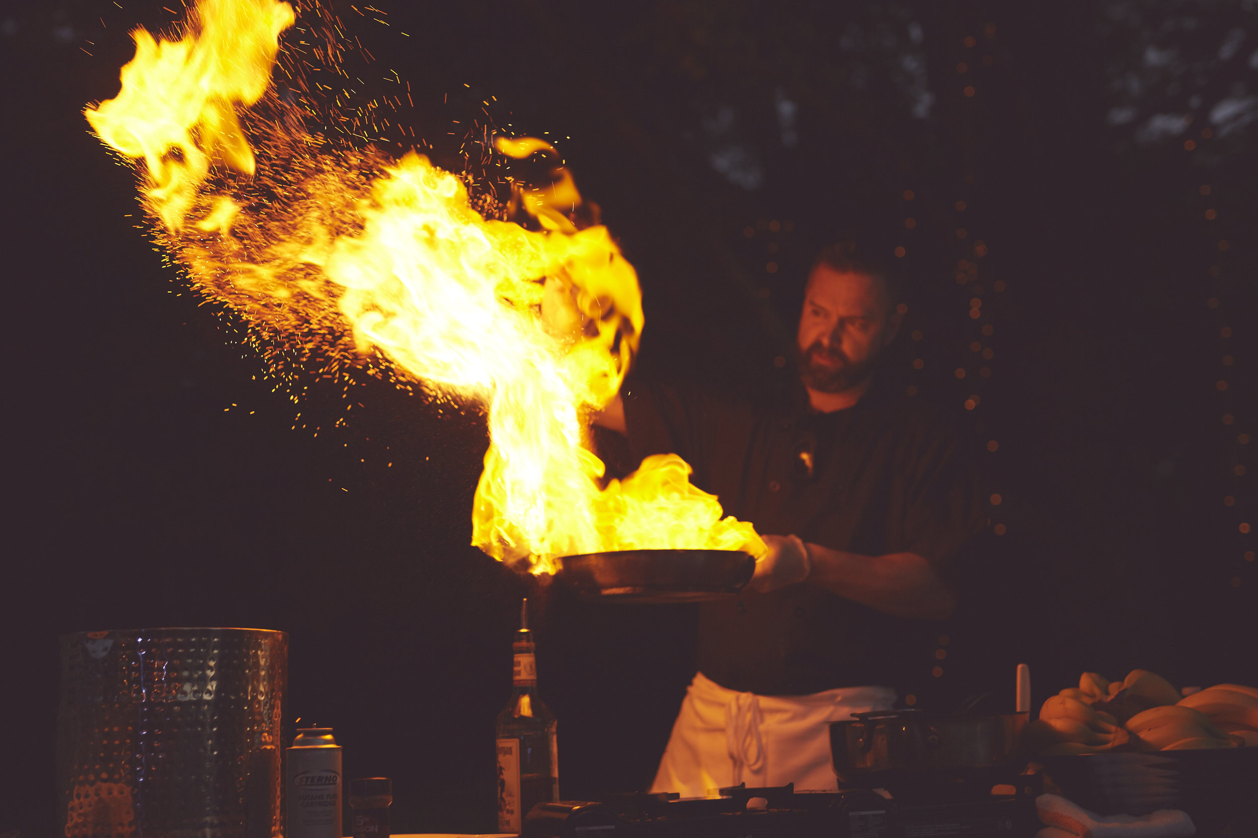 portrait of cook at event with big flame in pan