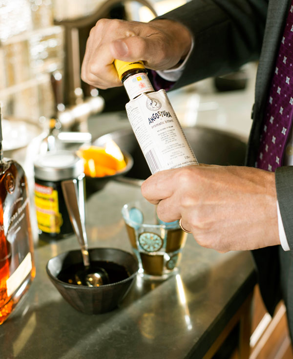 Add two dashes Angostura bitters and a 1/2 teaspoon of simple syrup to a lowball glass.