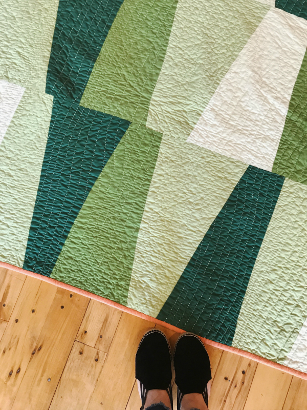 """This quilt was inspired by a Gee's Bend quilt owned by Cathy's daughter. Cathy made up this pattern, and calls it """"Lazy Tumbler."""" It's an improv quilt, with no measuring and no precision. """"This is the quilt that freed me,"""" said Cathy."""