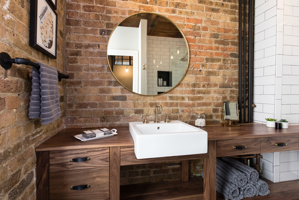 Can a bathroom be delicious? Michara's bathroom, with exposed brick, subway tile, an apron sink, grainy wood cabinetry, leather pulls, warm brass accessories, and gray pinstriped linens, is so yummy!