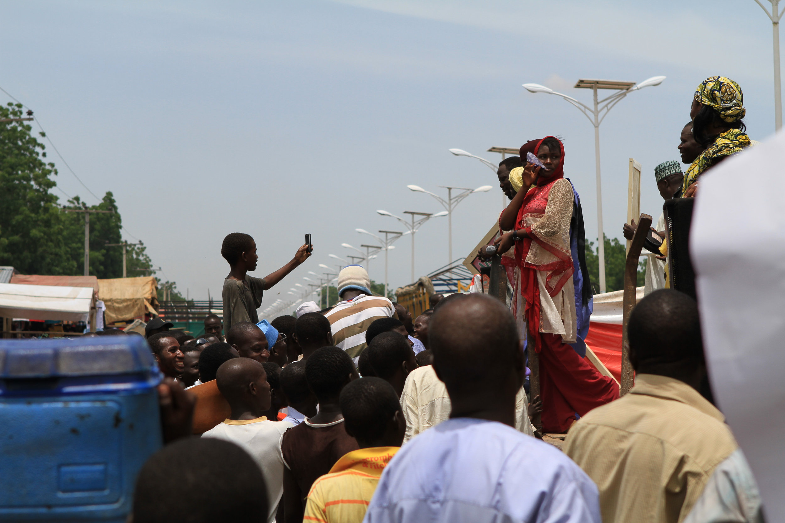 """Here, kids crowd around a truck during a """"polio rally"""". Performers sang as the truck drove around the streets of Maiduguri."""