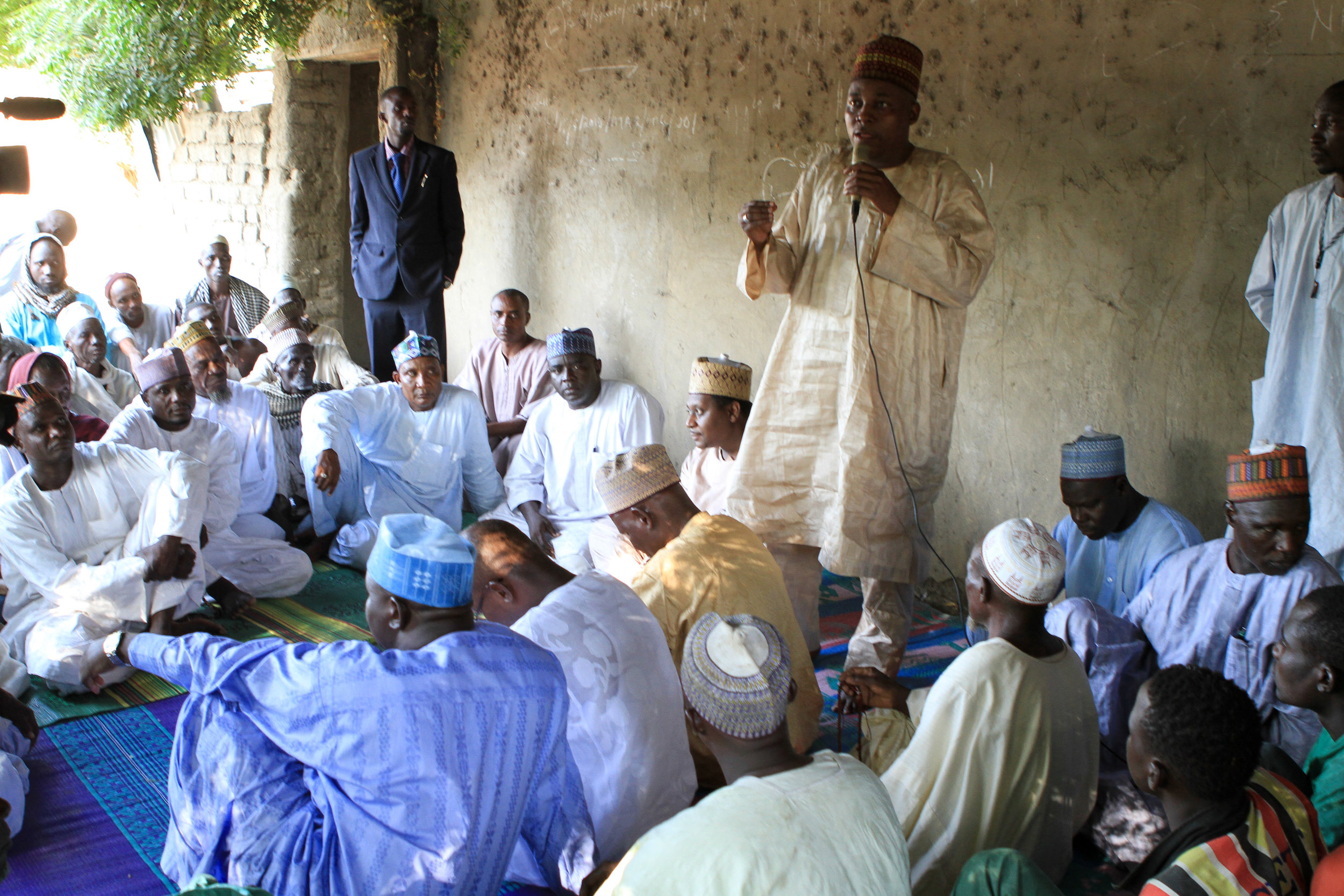 The men gathered around to discuss community needs, and t  he health minister promised them a health clinic.