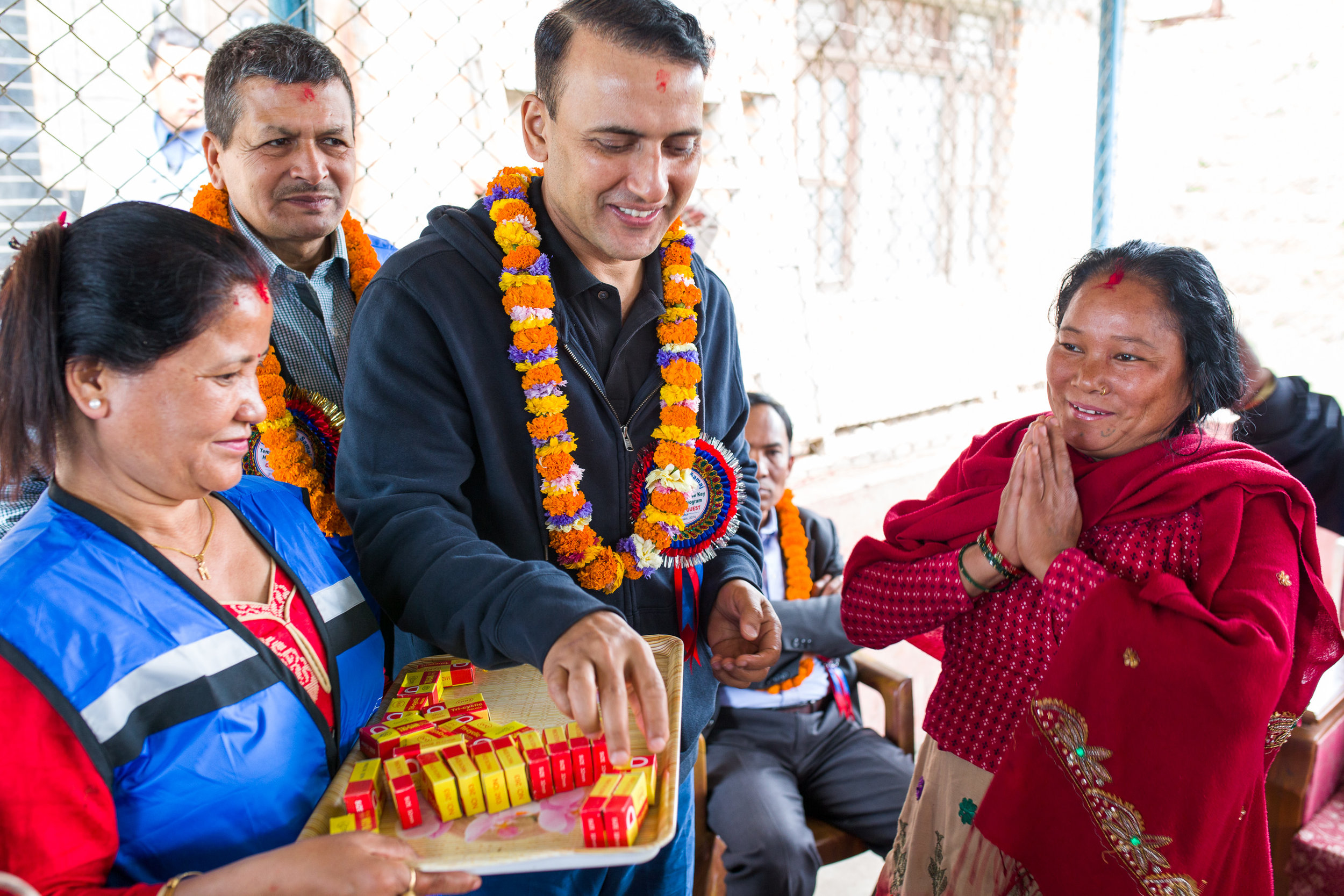 During a ceremony, Siddhi Aryal hands a symbolic key to one of the beneficiaries of the house-building project he and his wife Smriti helped to lead together with Nepali friends. Behind Siddhi is Pralhad KC, the Chairman of the Kavre Service Society (KSS) that oversaw construction of the homes.