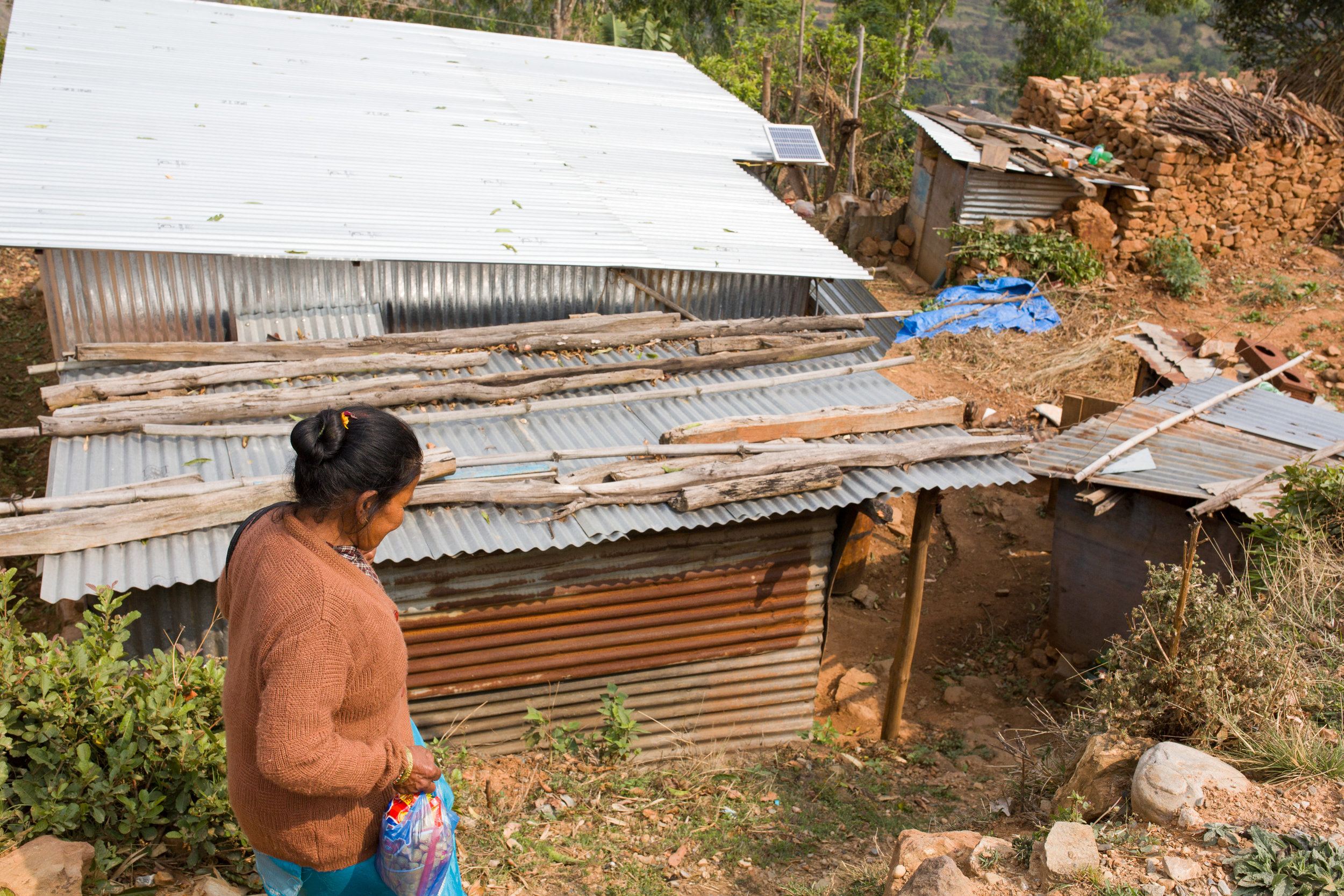 Keshari Napit walks down to her new temporary house, built by KSS with funds raised by Nepalis working outside the country. The house (with the uncluttered roof) has three rooms, solar lighting, a shaded veranda, and is constructed to withstand the monsoon rain and winds.