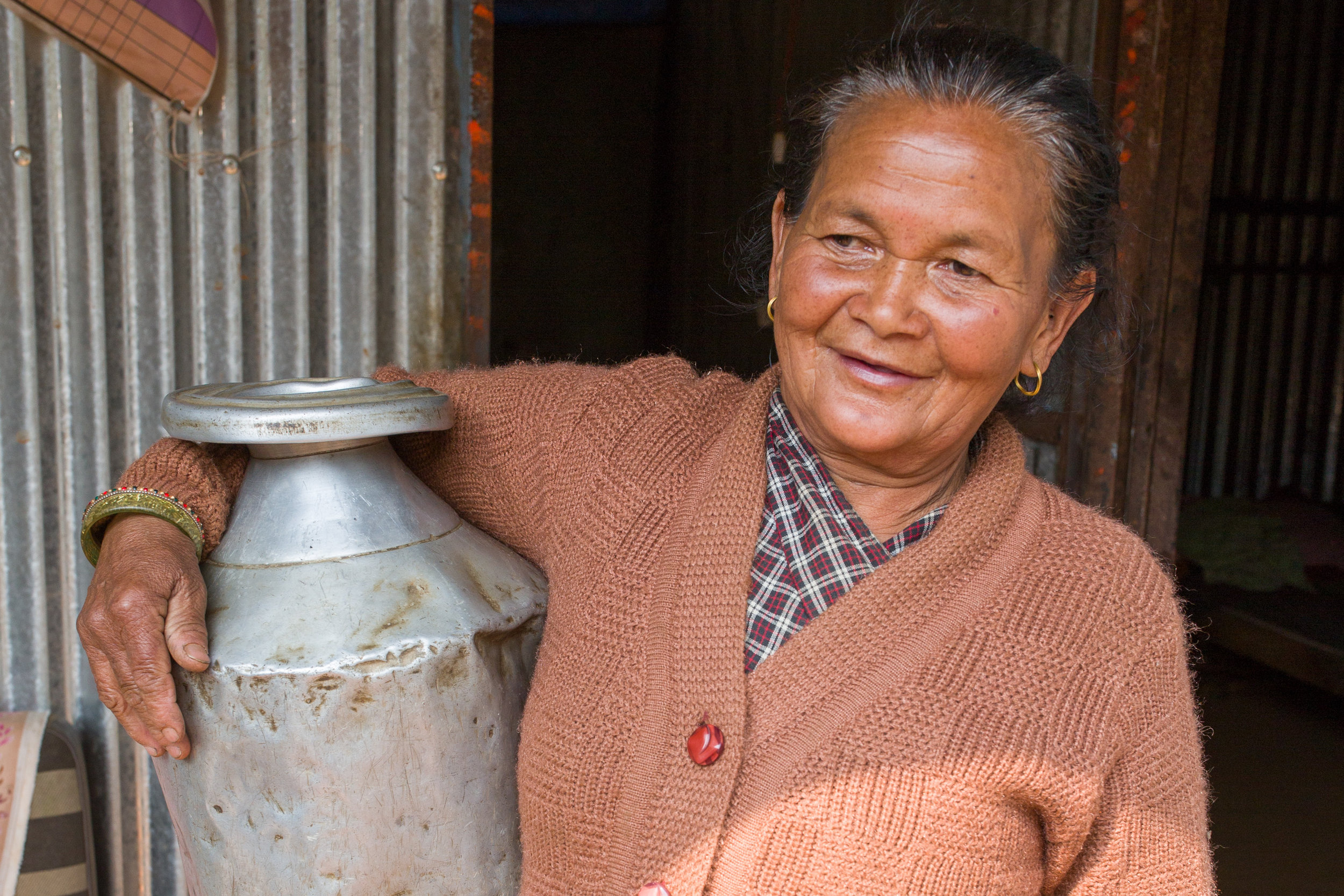 Keshari, a 74-year old widow, with a dented pot she salvaged from her crumbled home.