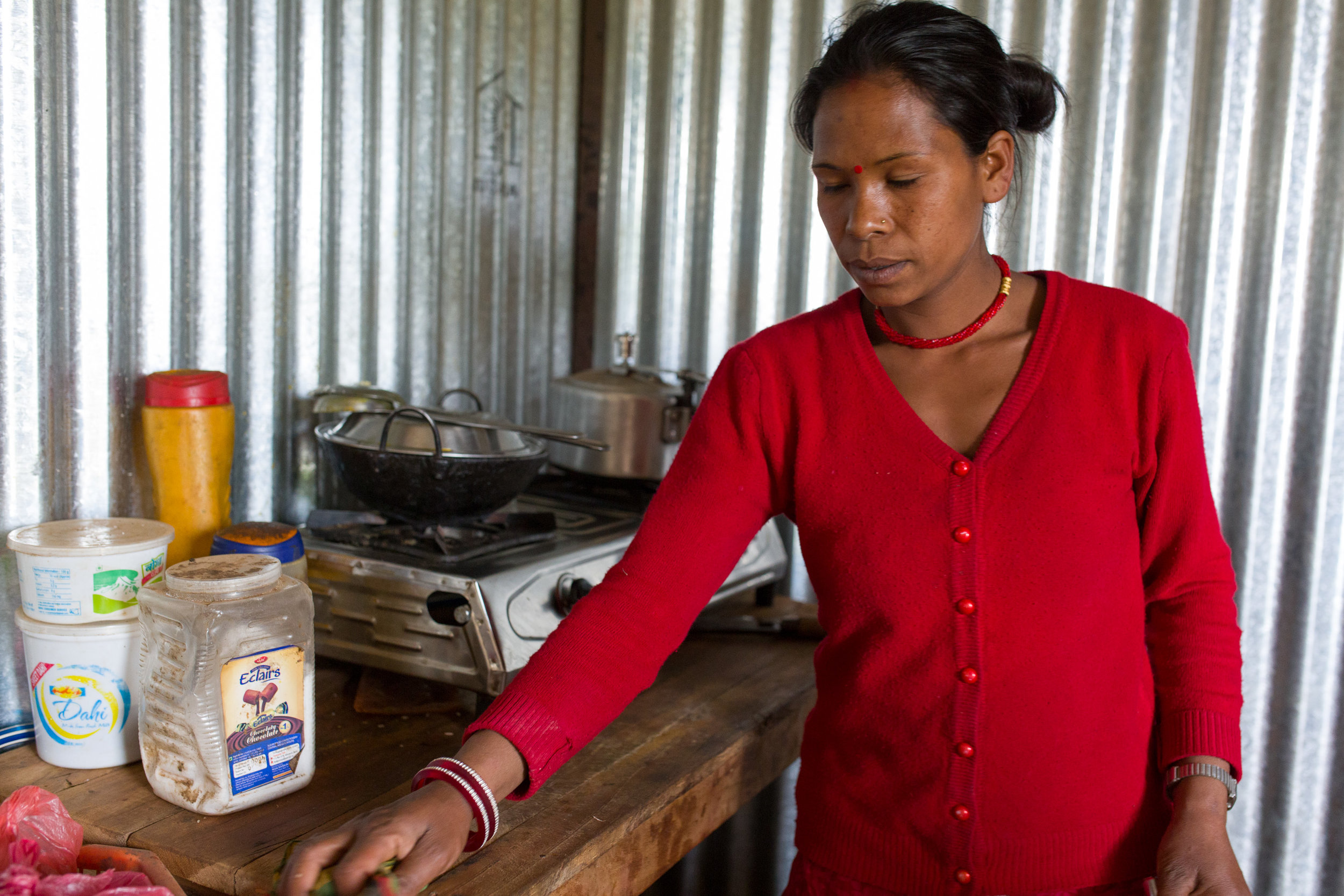 Niru washes up in her kitchen. She has no education, no identity papers and she doesn't own the land her house is built on. As a result, she doesn't think she can get access to government cash grants for a new house.