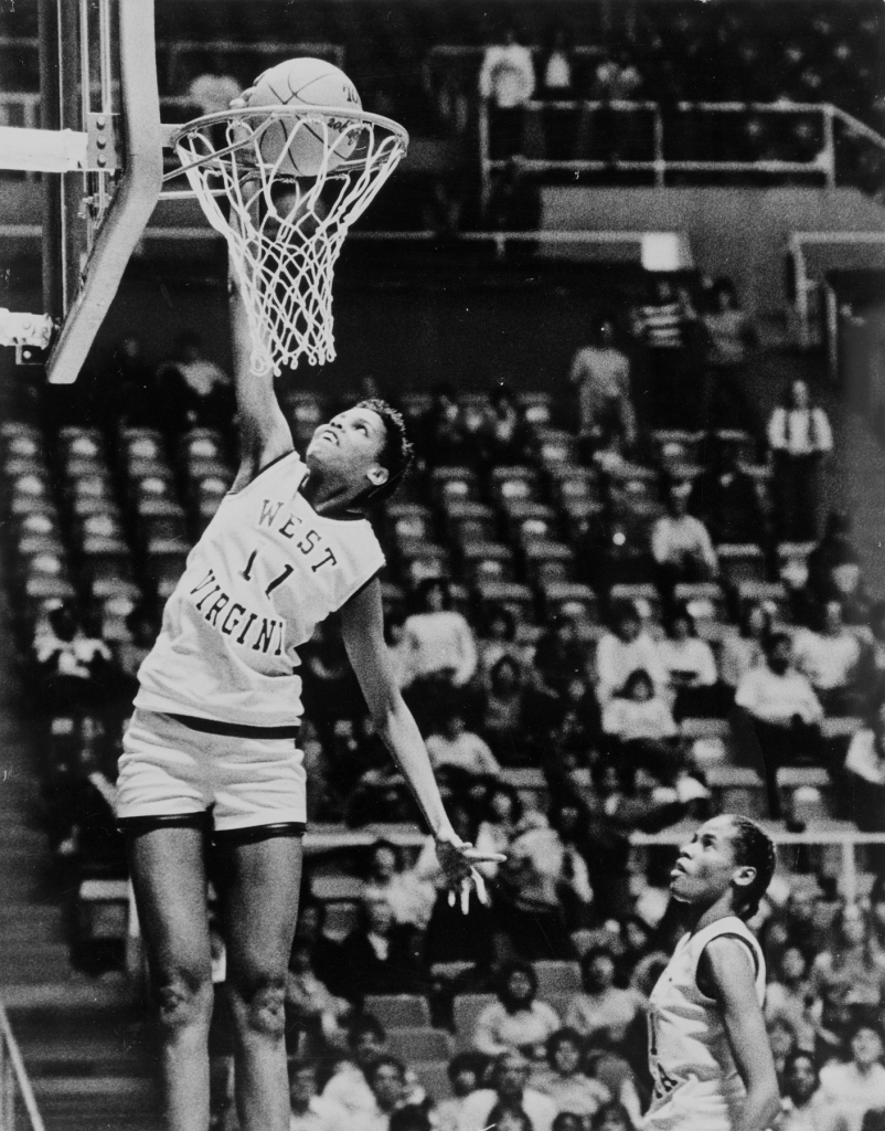 On December 21, 1984, 6 foot 7 inch West Virginia junior Wells became the first woman to dunk a basketball in competition.  It would be a full decade before another woman would do the same and 25 years before video proof of Wells' dunk was unearthed and made public. Following her college basketball years, Wells played professionally in Europe and toured with the Harlem Globetrotters.
