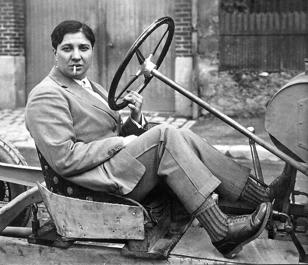 """Violette Morris competed in Boxing, archery, diving, javelin throwing, weightlifting, soccer playing, Greco-Roman wrestling, racing.Violette was famous for her athletic and automotive prowess, but she also drew attention by living openly as a lesbian, for dressing in men's suits, and for fistfighting during soccer matches. The French Women's Athletic Federation refused her request for a license renewal in 1927 and prevented her from participating in the 1928 Olympic summer games in Amsterdam. Violette made the news for electing to undergo a double mastectomy so she would be more comfortable behind the wheel. She ran an auto parts store in Paris until 1929.In the mid-1930s, Violette was recruited by a member of the Nazi security service and invited to Berlin for the 1936 Olympic Summer Games, where she was received by Adolf Hitler with """"much pomp and circumstance,"""" according to Jean-Francois Bouzanquet, the author of  Fast Ladies: Female Racing Drivers 1888-1970.  After that, it was straight downhill to an evil end for Violette Morris. It's said she provided Germany with information that helped the Nazis take Paris in 1940. She spied for the Germans, transported black market goods, and was said to be an active torturer of resisters. On April 26, 1944, she was ambushed by a dozen or so machine guns, by members of the French Resistance, while out driving in a supercharged Citroen."""