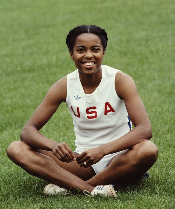 """Attending Roseville High School in California, Evelyn Ashford was invited to participate on the all male track team after a football coach noticed her during a phys-ed class and had her race his fastest player, saying """"I think you can beat him"""". She did, and joined the team. She later co-captained the team during her senior year and was one of the first female athletes to receive a full athletic scholarship in the U.S. During her time at UCLA, she won four national collegiate championships. Ashford competed in four Olympic games, winning four gold medals and one silver. Ashford was named Woman Athlete of the Year in 1979. At age 35, she participated as a member of the 4x100 relay team at the 1992 Olympics, becoming the oldest woman to win an Olympic gold medal in track and field. Ashford received the Flo Hyman Award in 1989 and was inducted into the U.S. Track and Field Hall of Fame in 1997."""