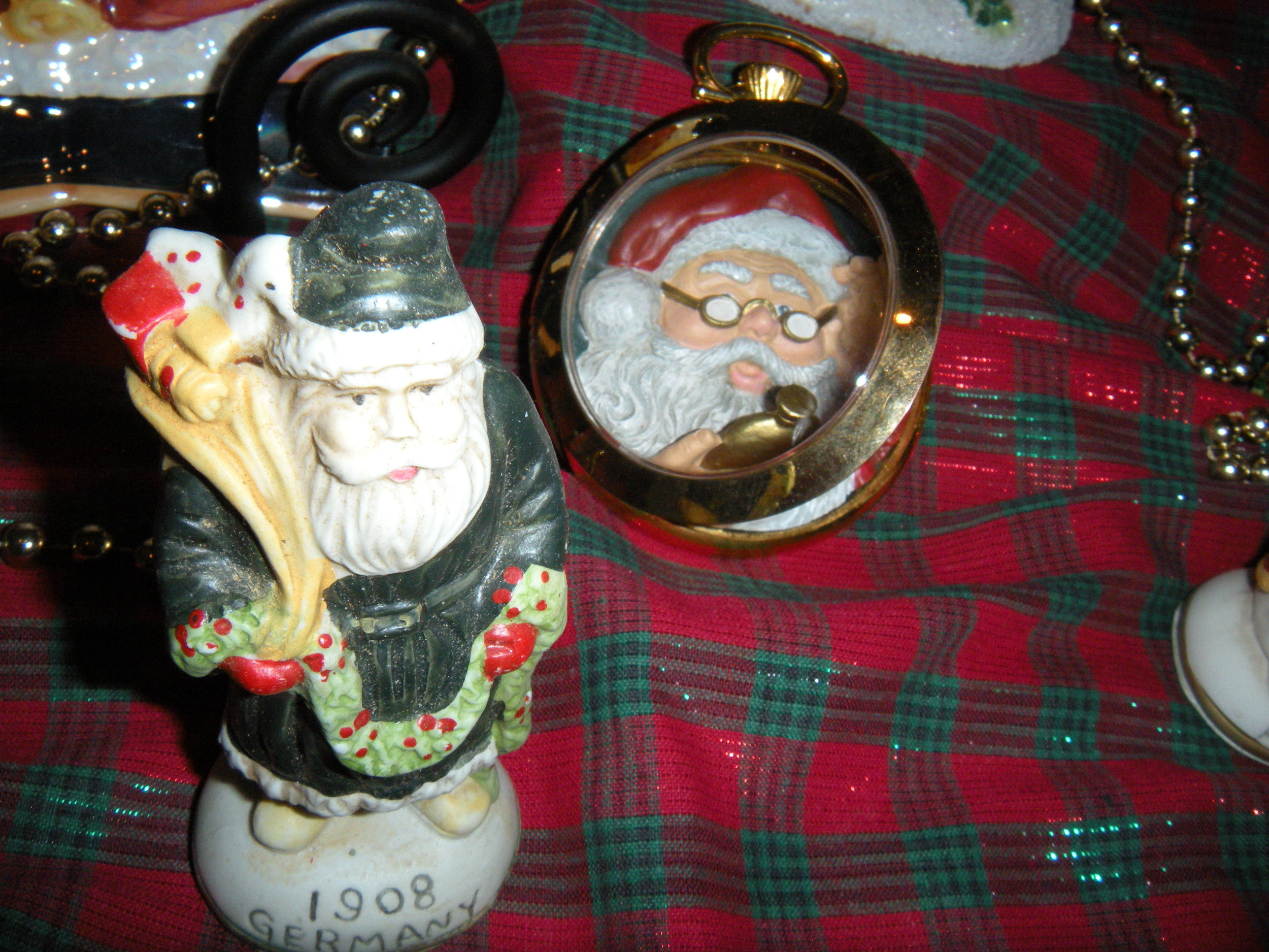I have a 1940's set of Santas from around the world. The Santa in the pocket watch is looking at his pocket watch. Clever, right?