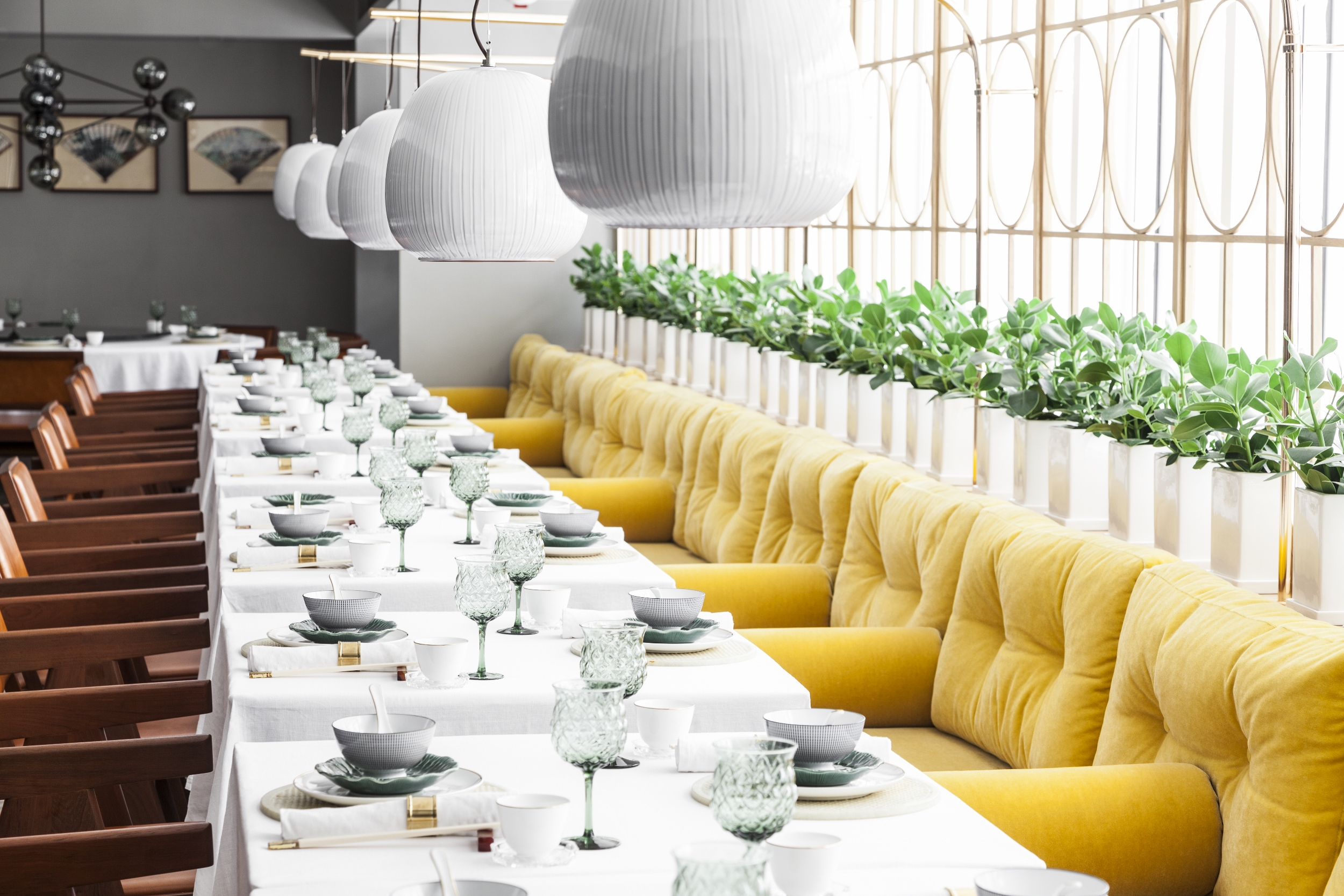 Plush leather chairs face yellow velvet banquettes in the airy third-floor dining room, lit by 'Gooseberry' pendants