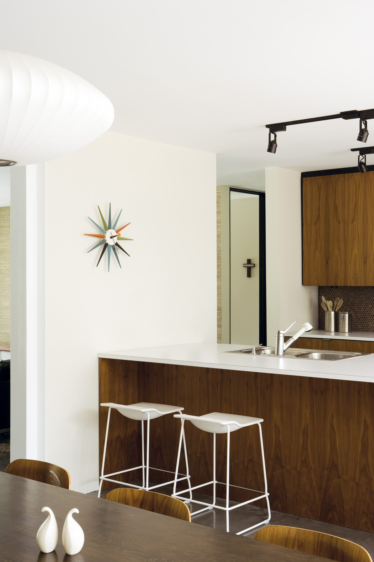 American diner: The kitchen at the end of the living room features sleek walnut cabinets and a multicoloured George Nelson 'Sunburst' clock