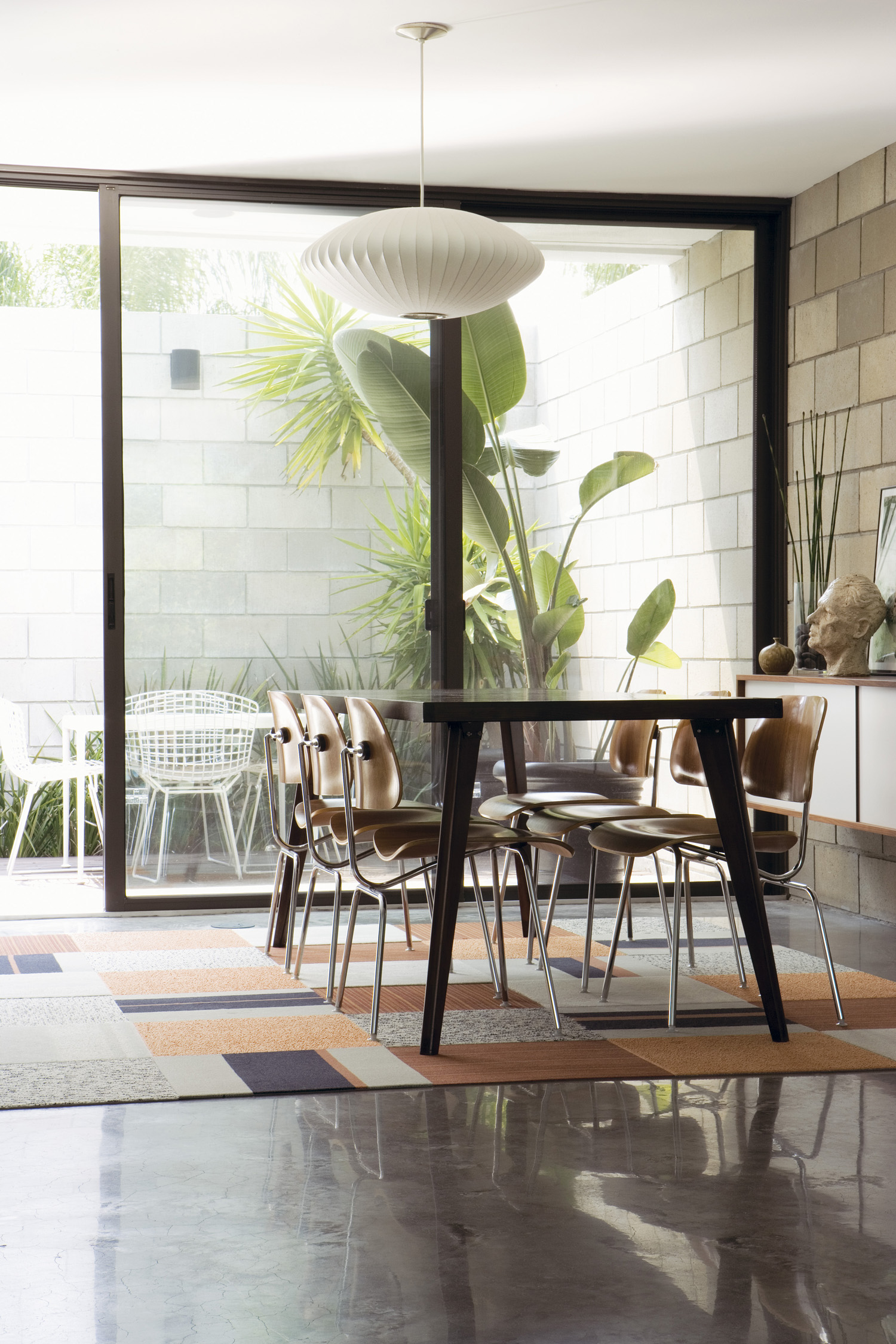 Inside out: The dining room opens out to a courtyard used for alfresco meals. Vintage Eames dining chairs and a George Nelson 'Bubble' lamp complement a table Brunson made from secondhand legs and a new plank of wood