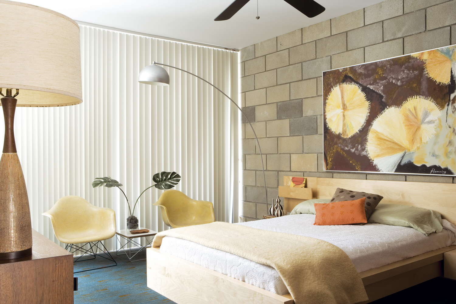 Mellow Yellow: The brutalist brick wall in the guest bedroom is softened with the addition of yellow Eames armchairs and a vibrant abstract painting. A vintage lamp towers above a dinky Eames 'LTR' table and a 'Credenza' cabinet by Florence Knoll