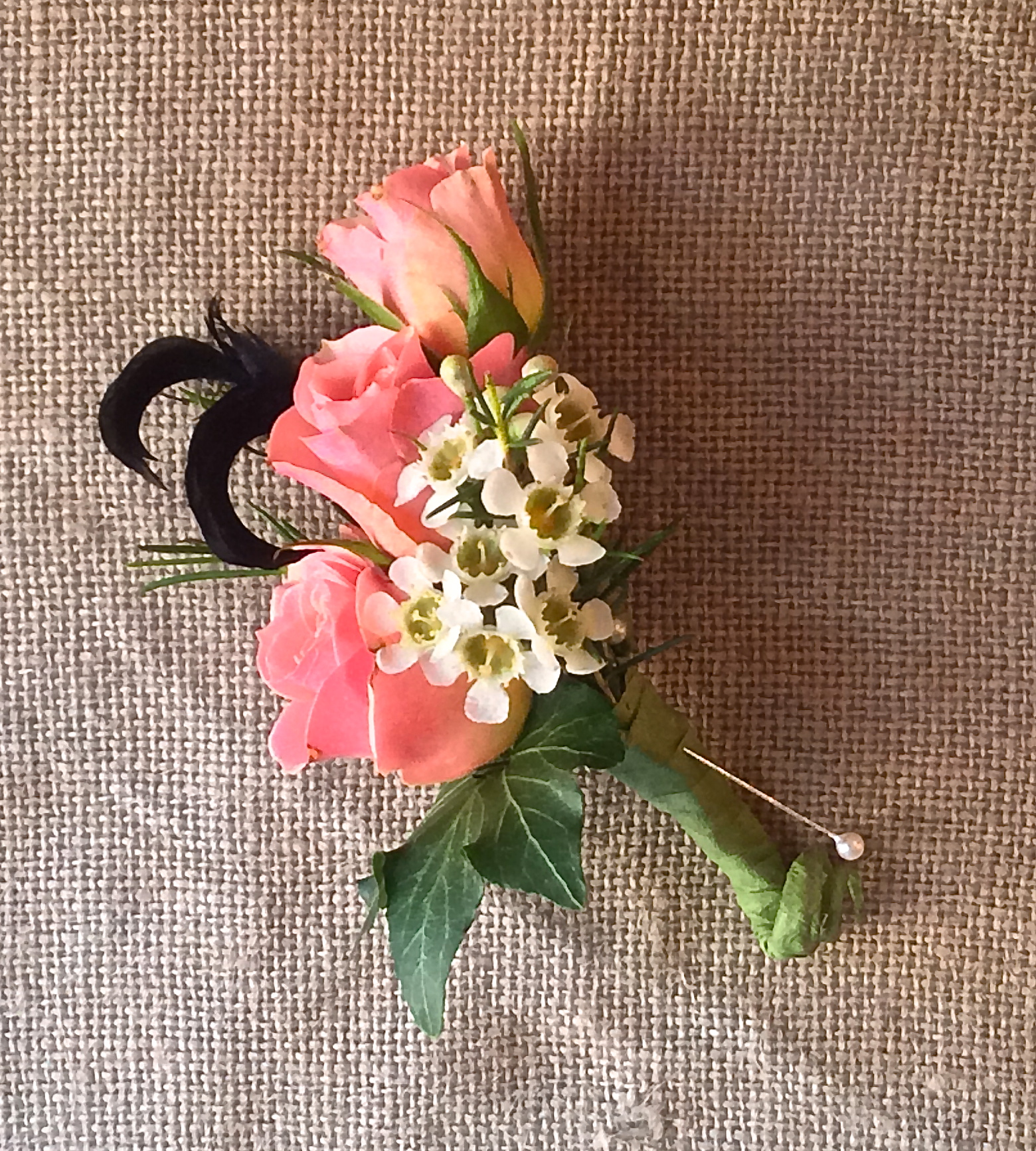Spray roses, waxflower, ivy and feathers.