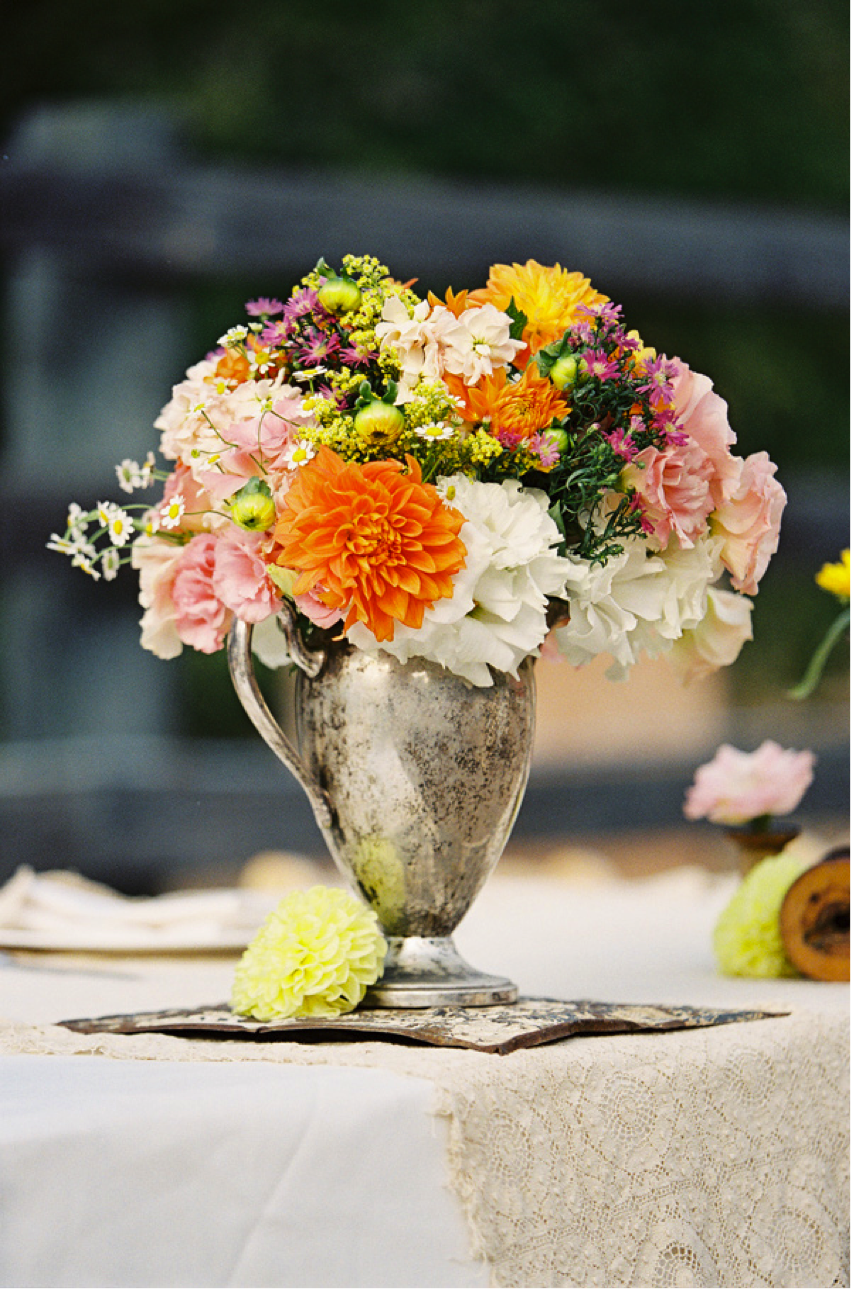 The silver vase is a great contrast to the bold and bright flowers ( Via }
