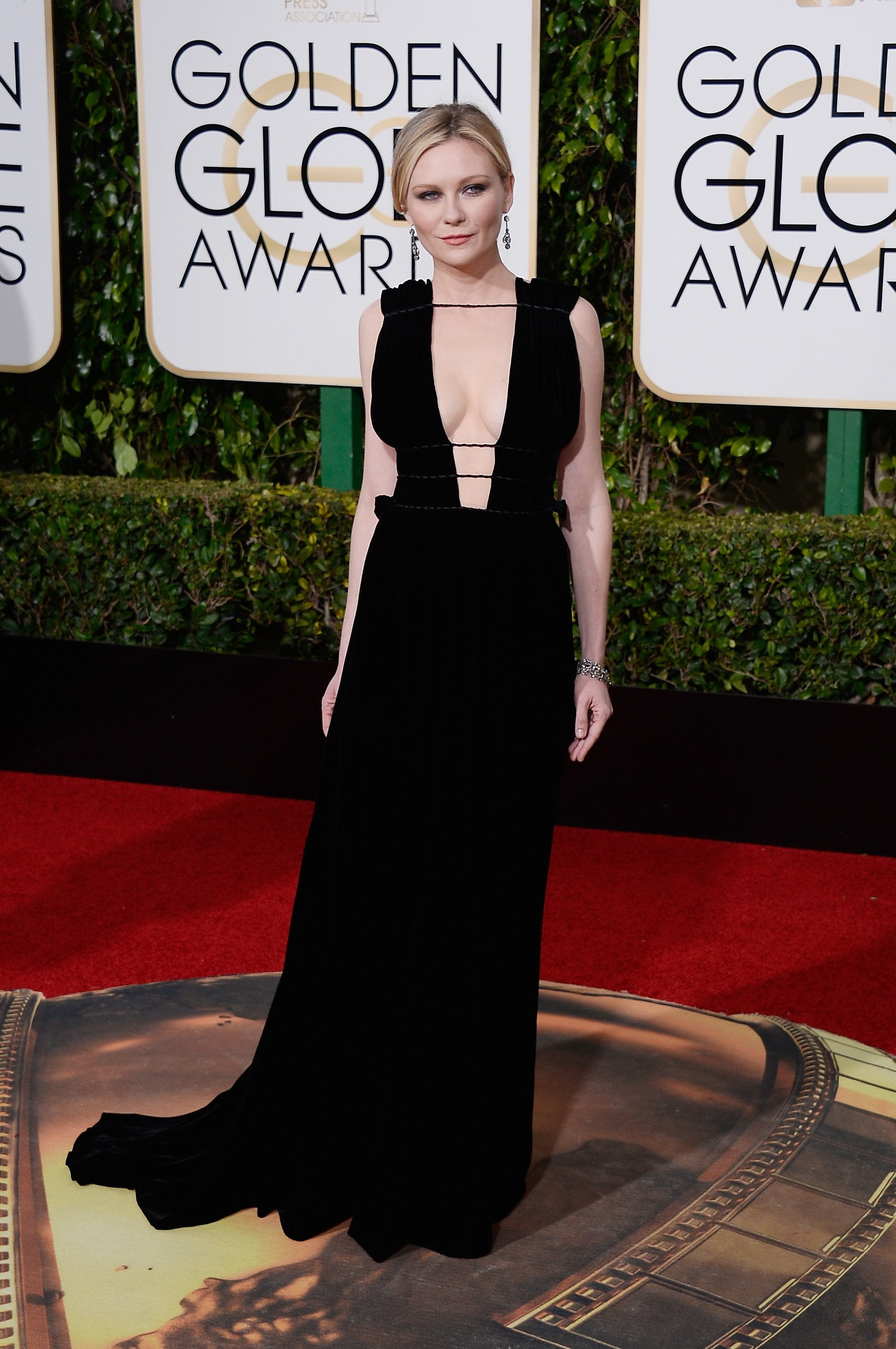 """Brr, it's cold in here I said there must be some"".... Kirsten Dunst at the Golden Globes! She is rockin' this Valentino plunged neck line gown. Never can go wrong with black, or Valentino!"
