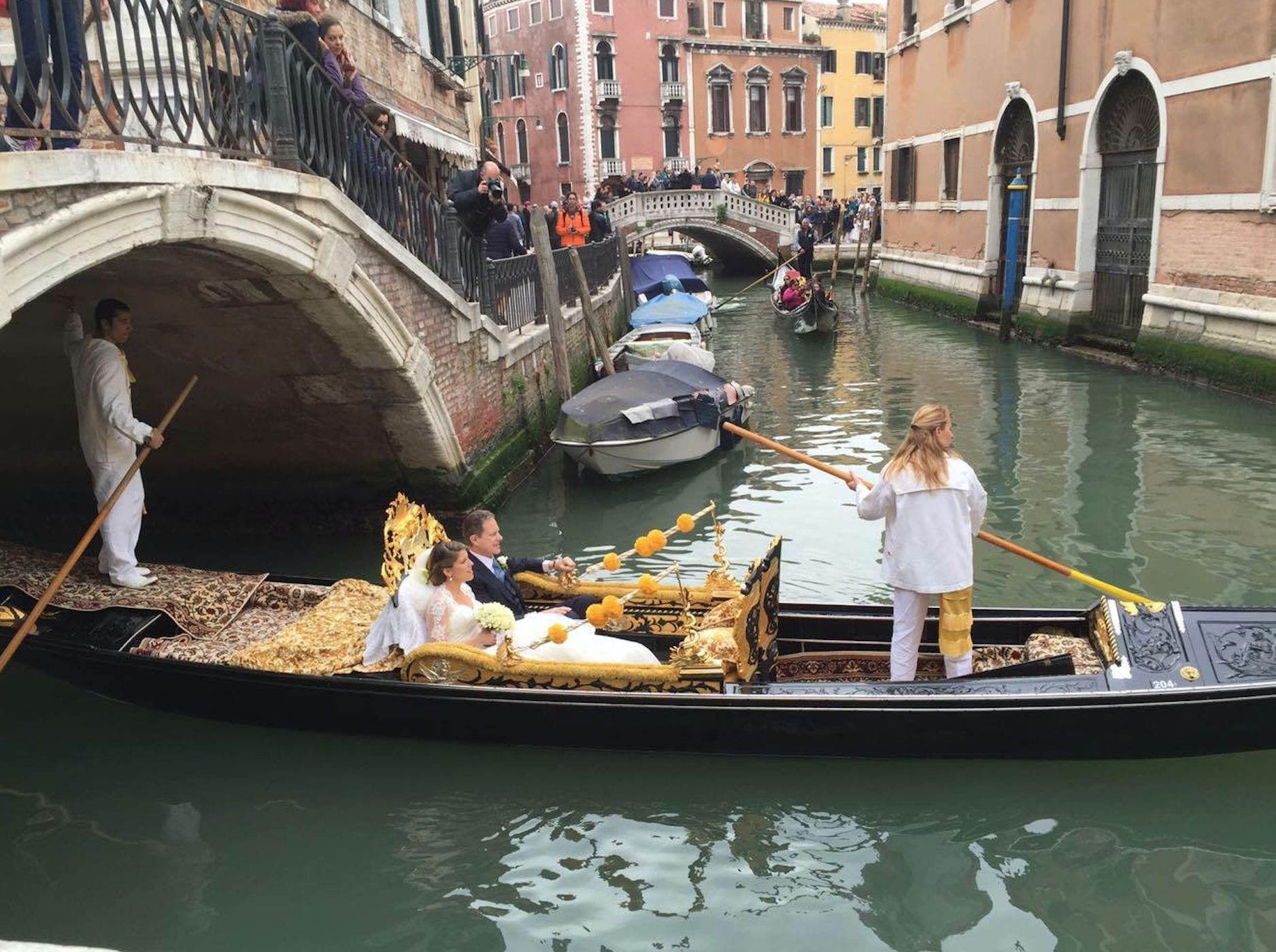 """This beautiful bride is getting married in Venice, Italy. The bride and her father are doing the traditional Gondola ride through the canals of Venice to the church. All of the guests are standing on the bridge and above her to welcome the bride and her father to the church. Some traditional brides in Italy, however, will replace the """"something blue"""" with a green dress or accessory."""