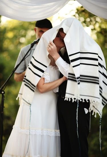 At a traditional Jewish wedding ceremony, the bride and groom will share their first kiss under a prayer shawl.