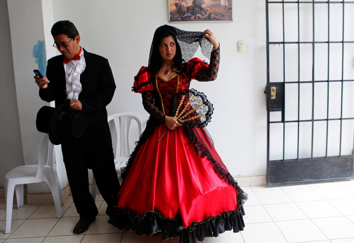 In Lima, Peru, you will see traditional brides in bright red and black gowns, these gowns are often very large and heavy due to the multiple layers of cotton and heavily embroidered petticoats used to give the dress a flared look at the bottom. The veil is also traditionally black lace and short.