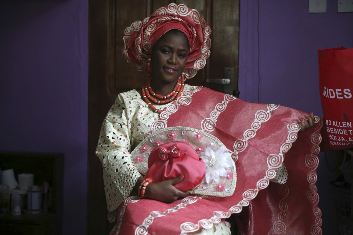 This beautiful Nigerian bride is traditionally dressed in a brightly colored lace blouse and patterned kaftan. She has on coral beads and a headdress to bring the wedding attire together.The bride can decide on what color she would like her blouse and kaftan to be and matches her beads and headdress accordingly.