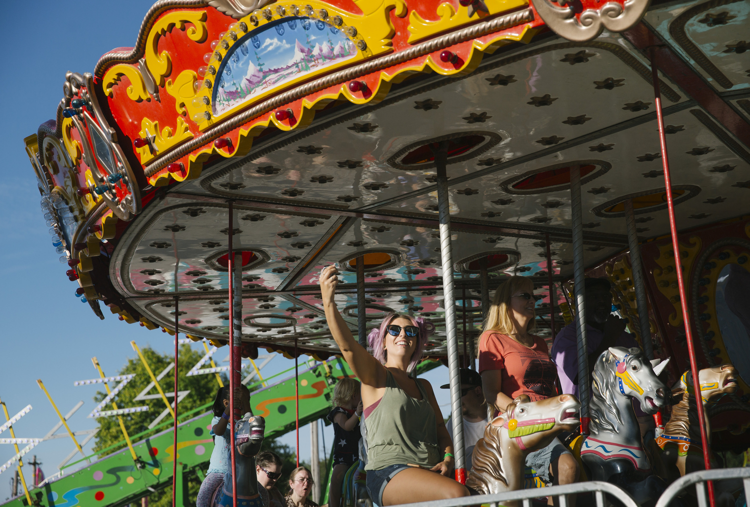 Fairgoers ride the carousel at the Ozark Empire Fair in Springfield, Mo. on July 29, 2017. Photo by Brad Zweerink.