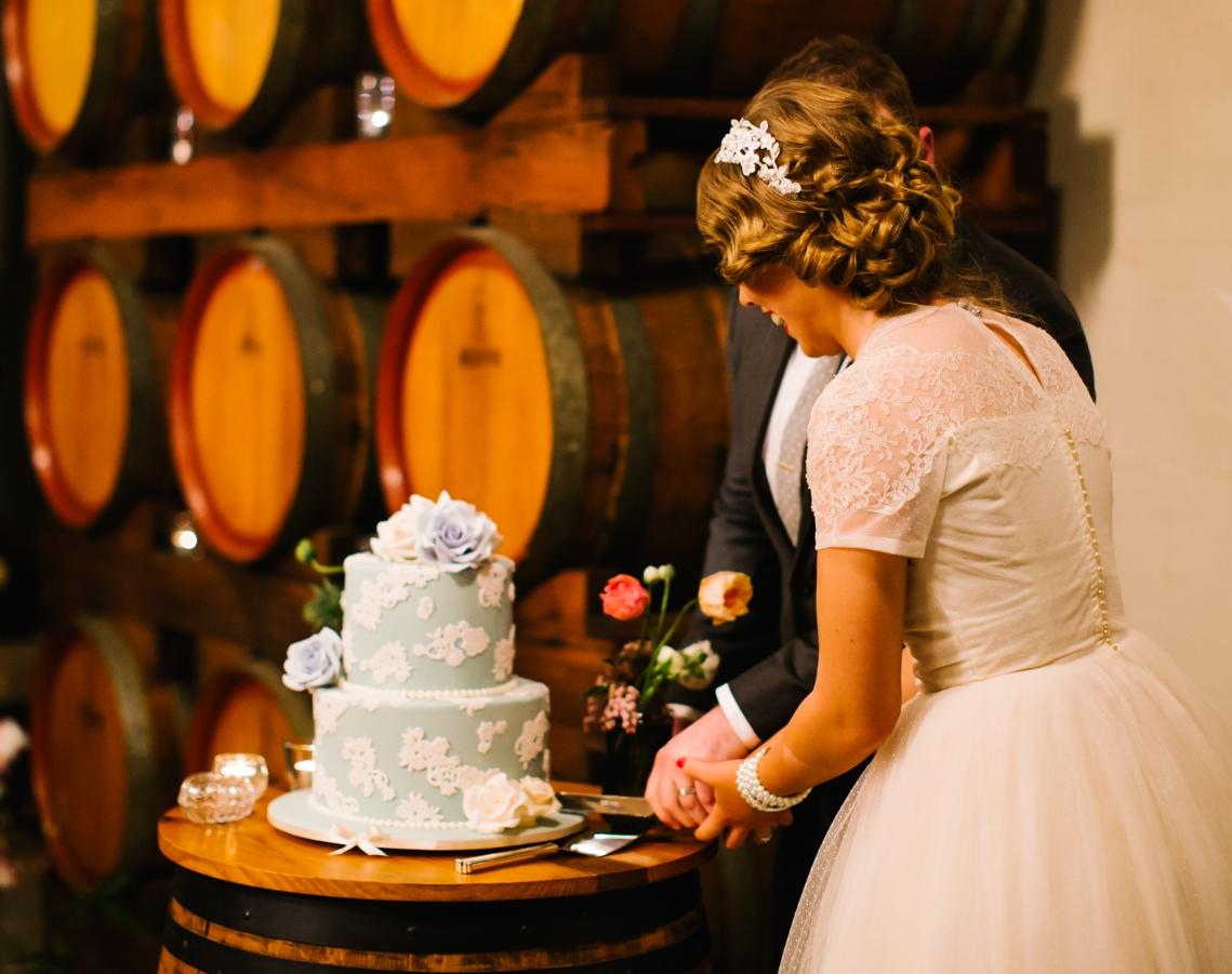 "Craig and Elyssa cut their vintage style wedding cake, at Wyndham Estate. Photograph courtesy "" Mark and Kara Photography ""."