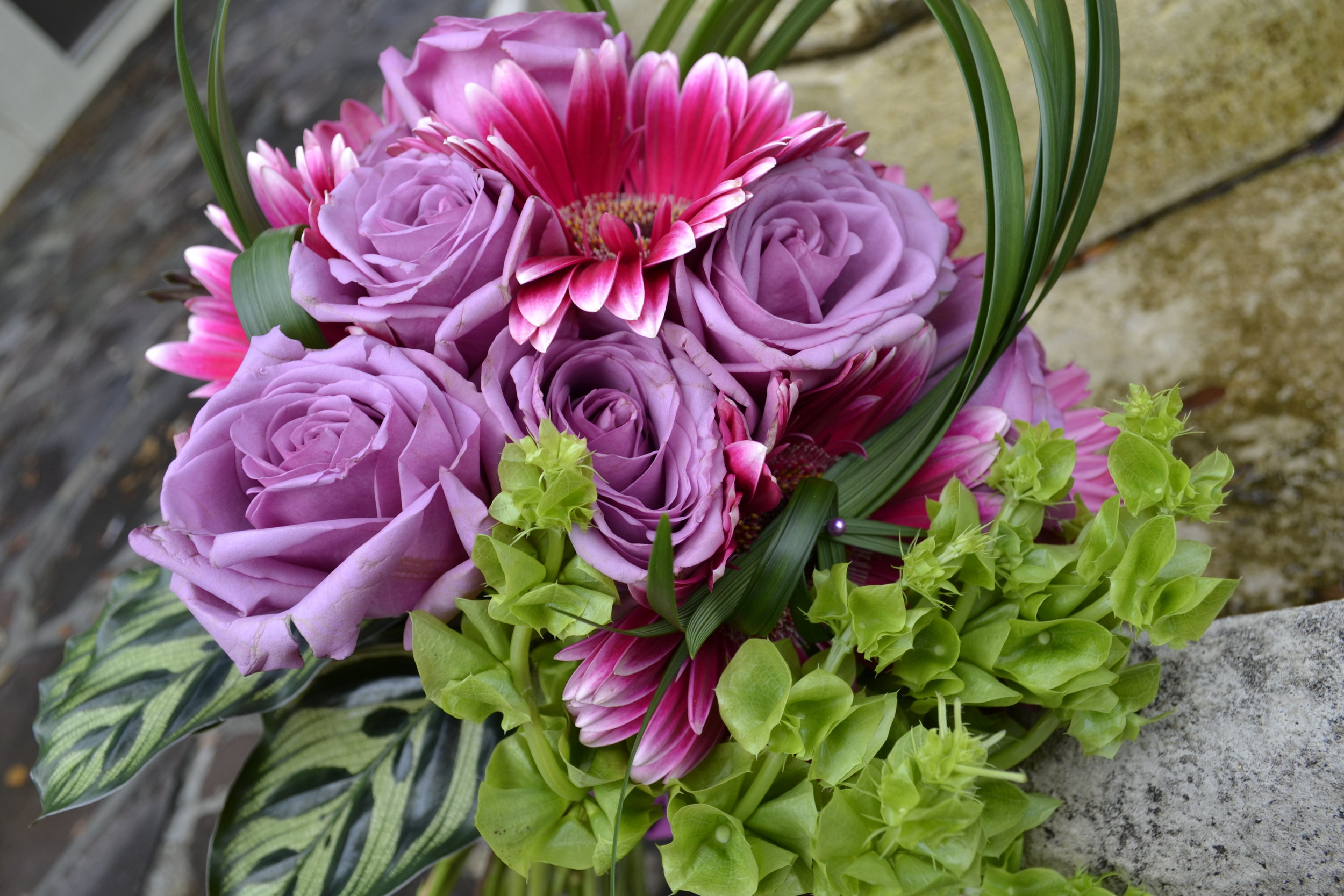 A vivid color like the hot pink floral focal points add a pop of interest to the lavender and green bouquet.