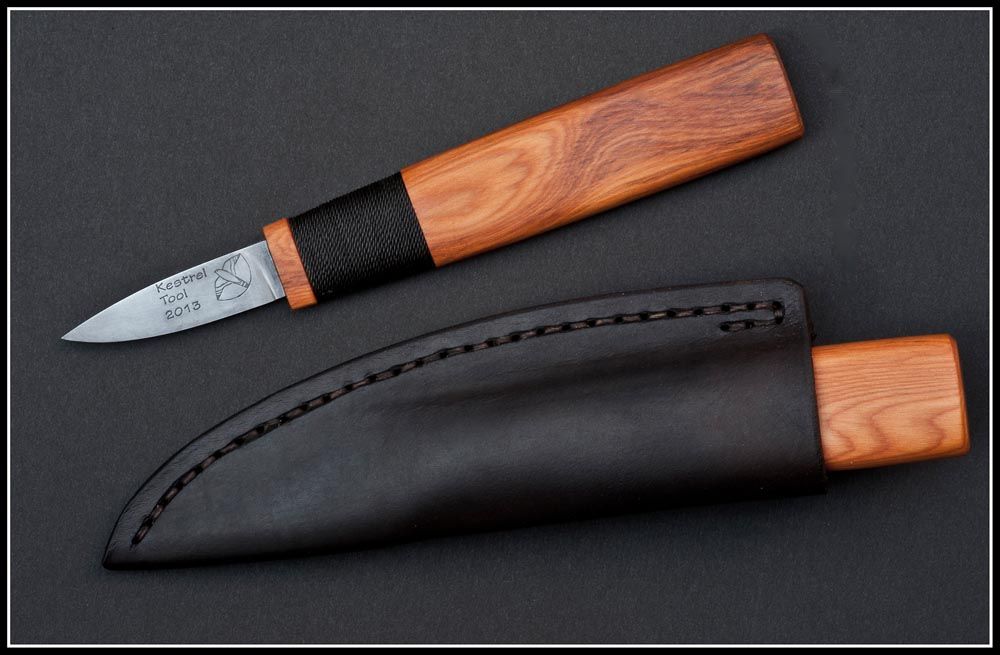 Deluxe-grade Kestrel Straight Knife in Yew wood, with logo and hand-sewn vegetable-tanned Turkish leather sheath