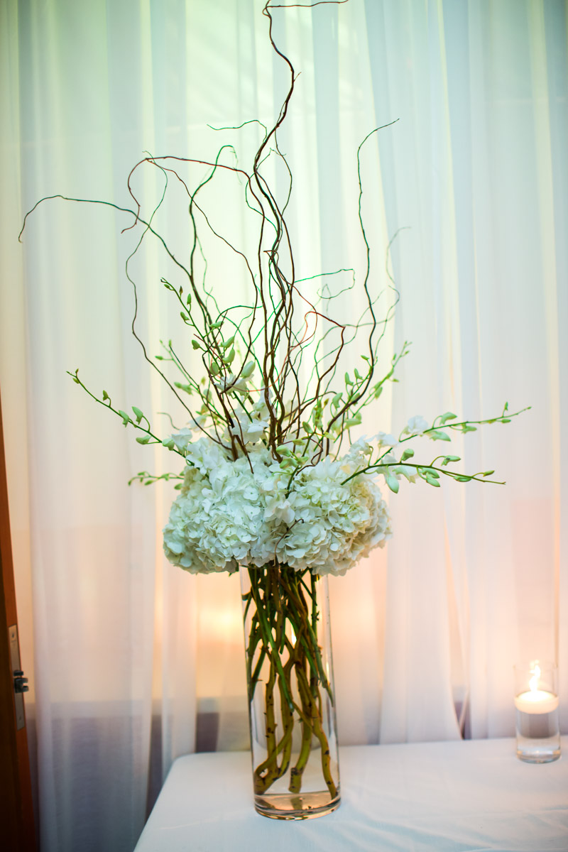 We made a tall arrangement with curly willow, white hydrangeas, white dendrobium orchids for the escort table.