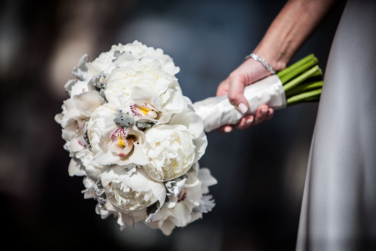 Kate carried a bouquet of white flowers: white peonies, white cymbidium orchid and accented with dusty miller and wrapped with ivory satin ribbon. Matching her simple and elegant dress.