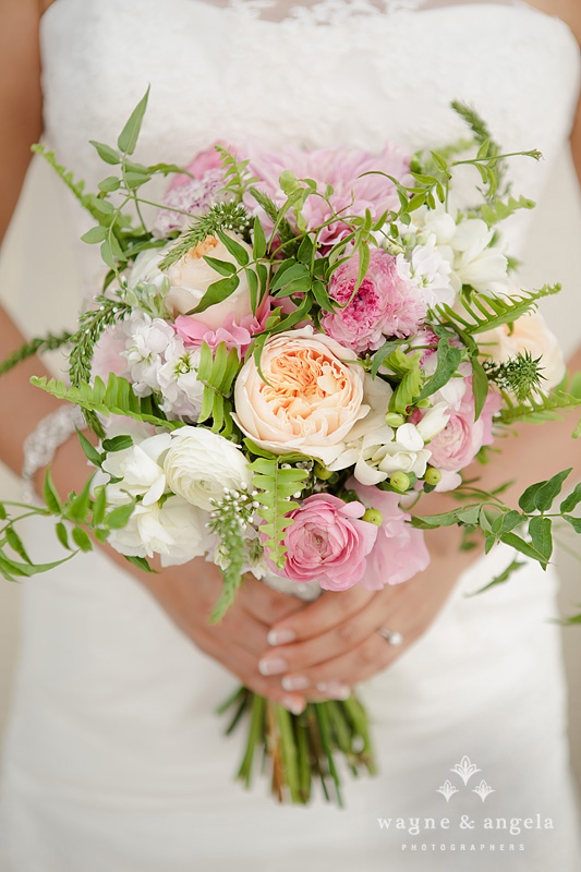 "oyce carried a bridal bouquet of pink and peach flowers: pink/peach "" Juliet"" garden rose, white ""polo"" roses, white ranunculus, white sweetpeas, pink dahlia, Jasmine vine, sword fern and lysimachia."