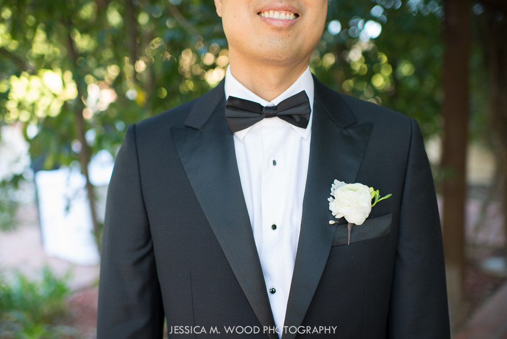 Peter wore a white ranunculus boutonniere accented with white freesia and dusty miller.
