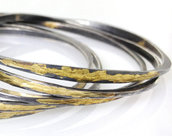 Oxidized sterling silver bangles with 14 karat yellow gold forged onto the surface.