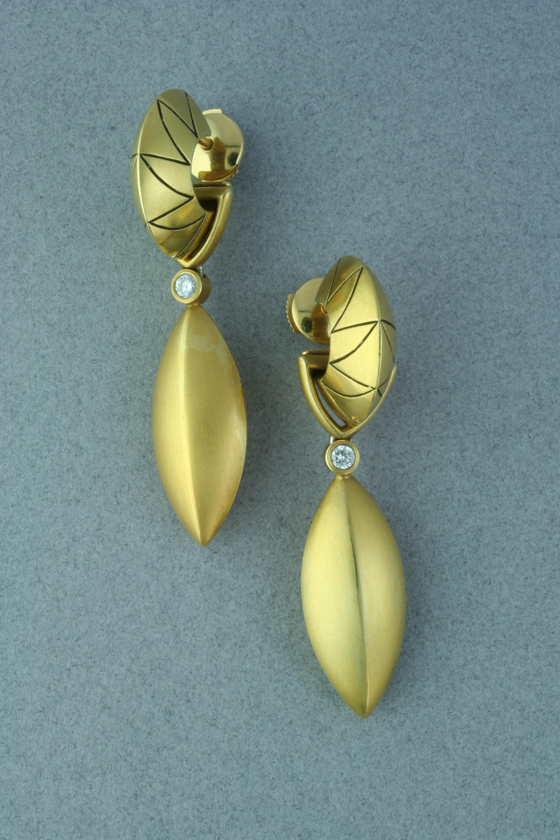 """18 karat yellow gold engraved hoop earrings each with a detachable 18 karat yellow gold """"Fish"""" dangle. Two diamonds, 0.14 cttw , VS-SI in clarity top each """"Fish."""""""