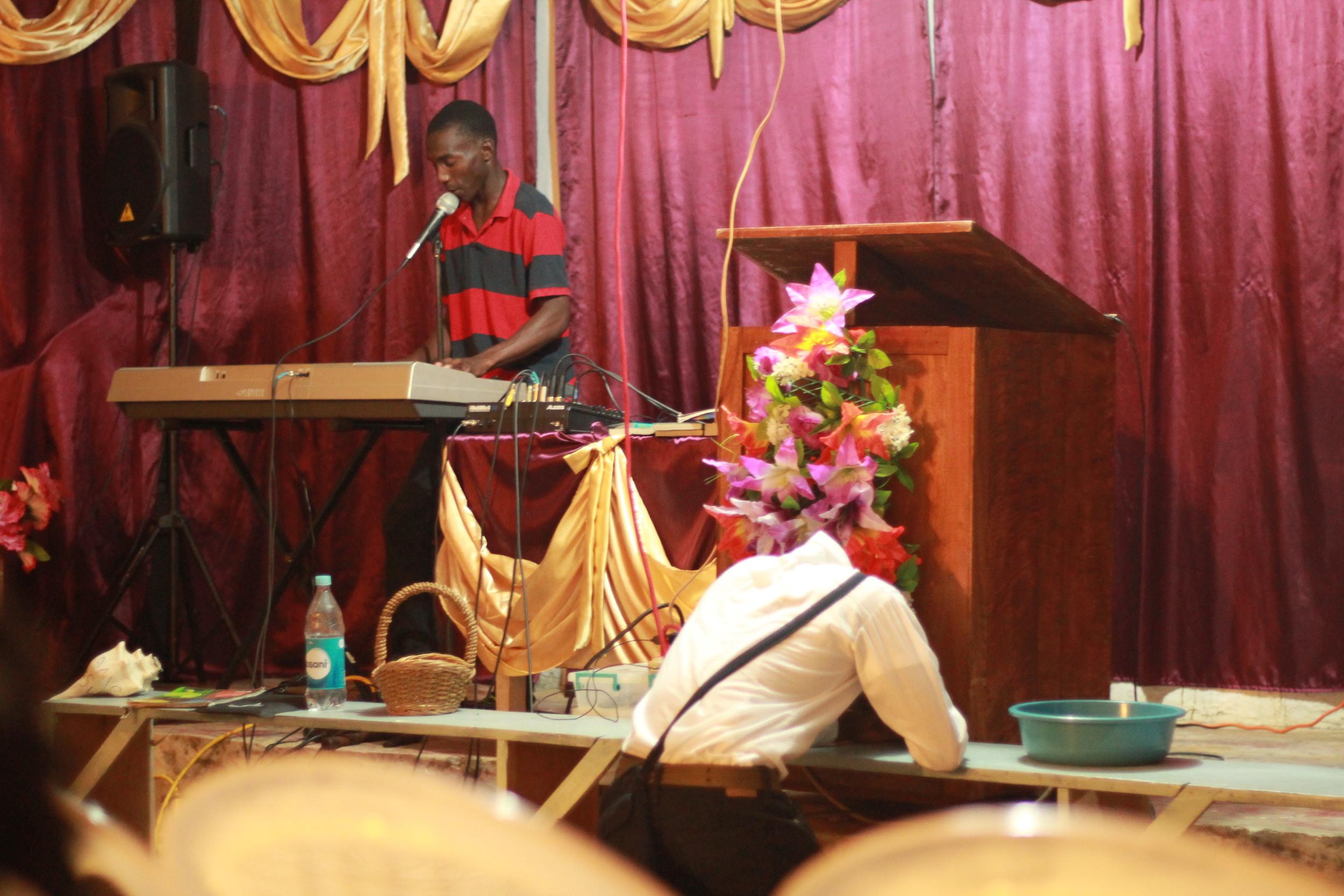 Pastor Adonis singing in the church in Cusuna