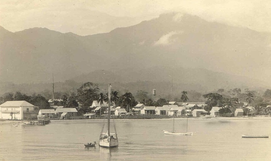 "Partial view of La Ceiba waterfront in the 1910s. The sender of this real photo postcard, possibly an American missionary, describes the white building behind the boat's mast as ""our church"" and the large building at the left as the barracks and prison.The wireless station and tower to the right of the water tower belonged to ""an American banana company"", most likely the company that became the Standard Fruit Co. and whose operations were headquartered in La Ceiba. Unknown, c. 1915 - Public Domain"