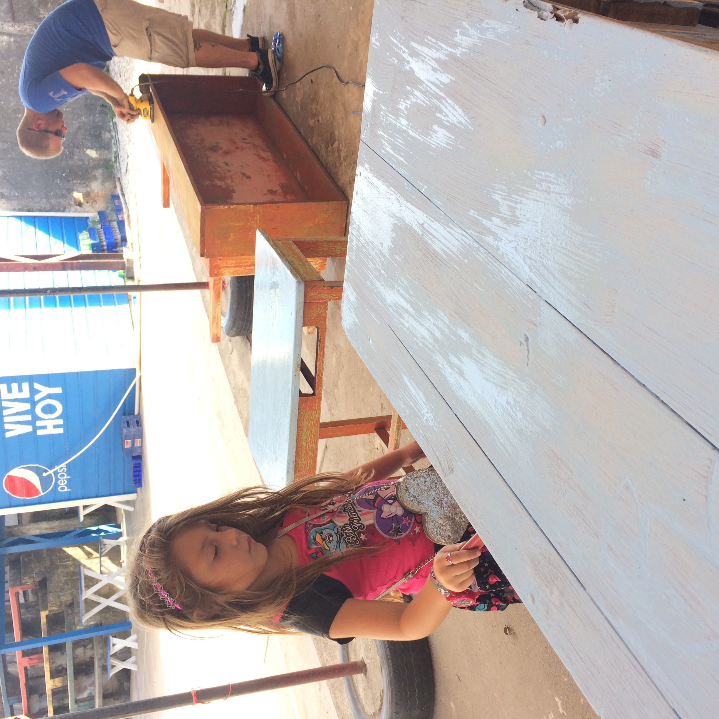 Saige Mendoza (Foreground) helps refinish a desk for the classrooms at DINAF in La Ceiba Honduras