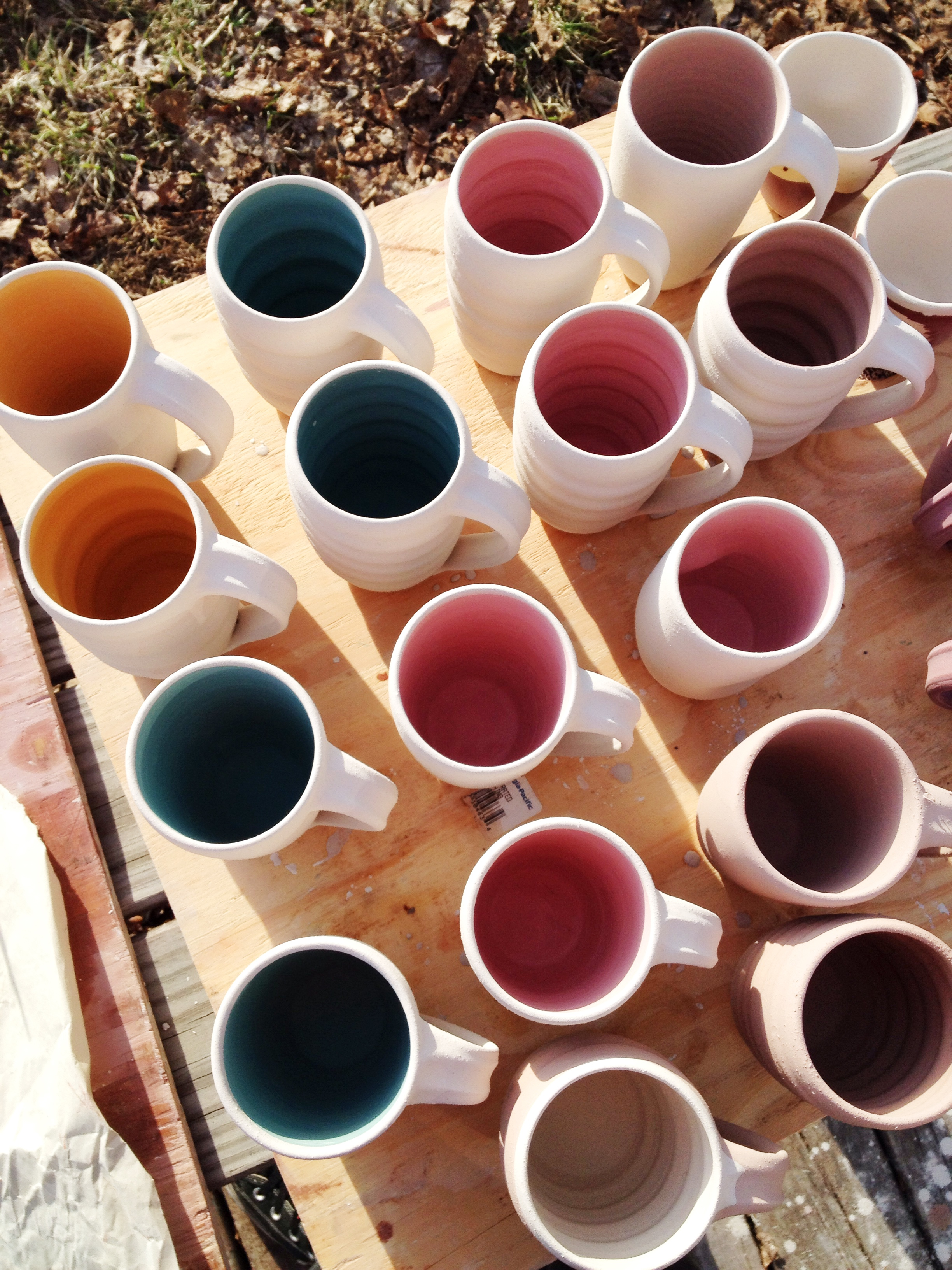 An assortment of the new smooth-sided mugs and the classic ripple mugs, glazed with bright pops of color on the interior and a soft cream on the exterior.