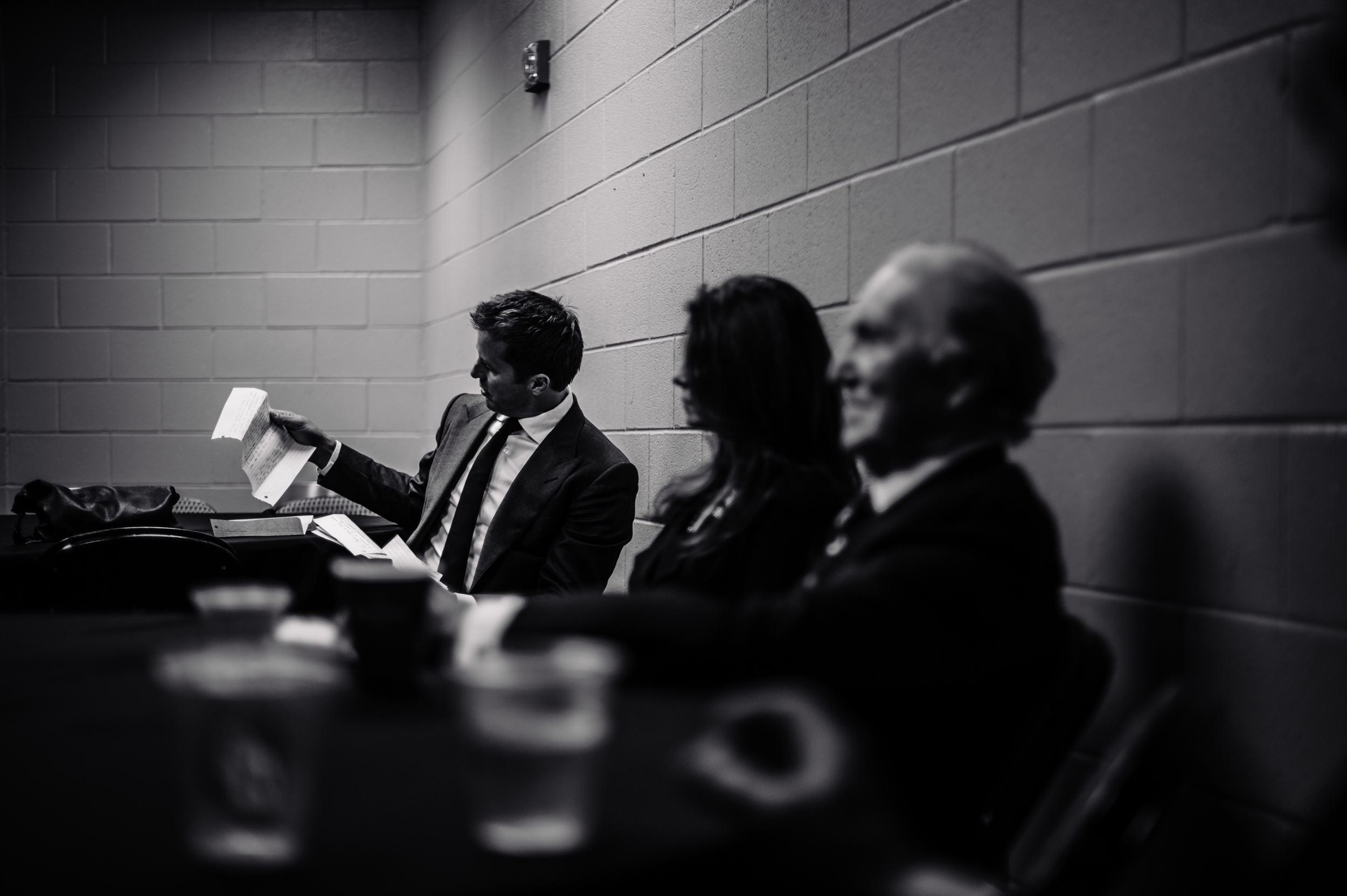 Mike Modano looks over his notes in the green room, as former Dallas Stars owner, Norm Green, looks on.