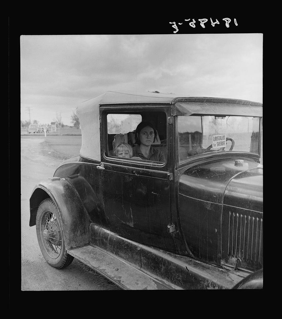 During the cotton strike, the father, a striking picker, has left his wife and child in the car while he applies to the Farm Security Administration for an emergency food grant. Shafter, California.