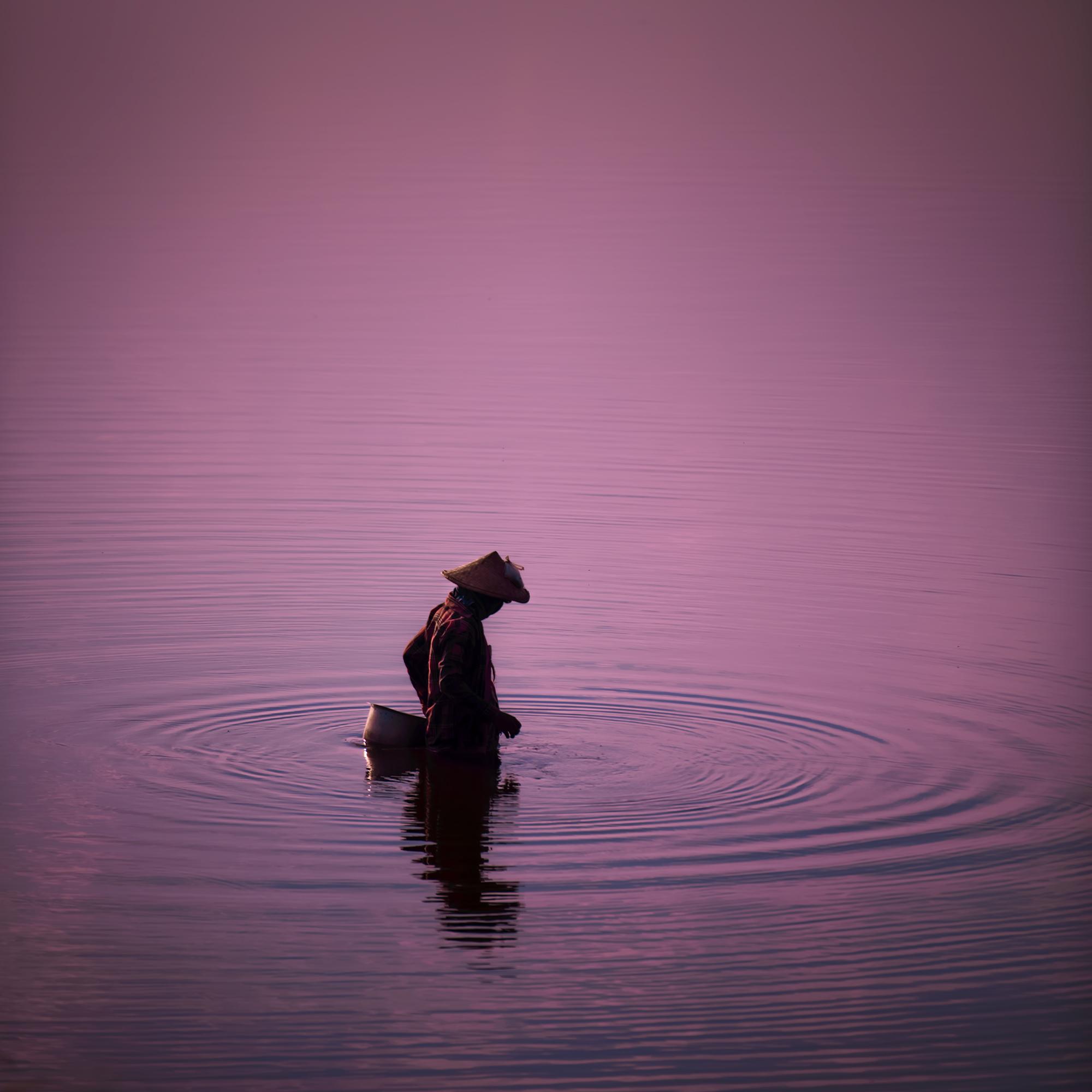 A fisherman  slowly wades through the water near U Bein's Bridge.