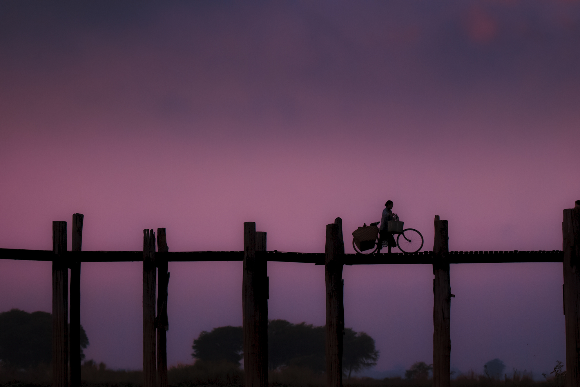 A woman  walks her bike across U Bein's Bridge at sunrise, carrying her goods to market.