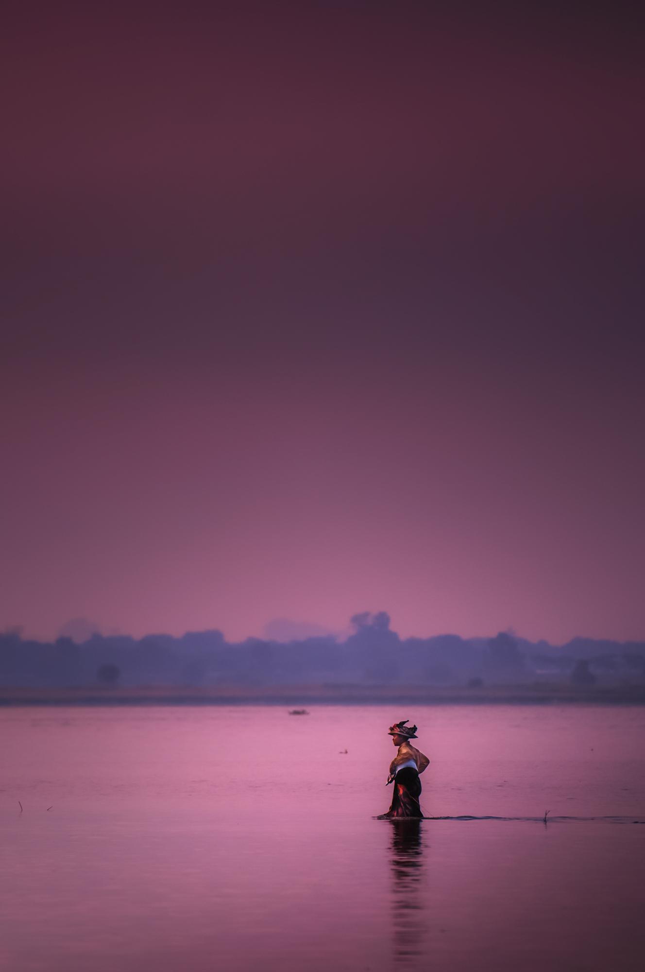 A woman wades  through the water beneath U Bein's bridge toward more fertile fishing grounds.