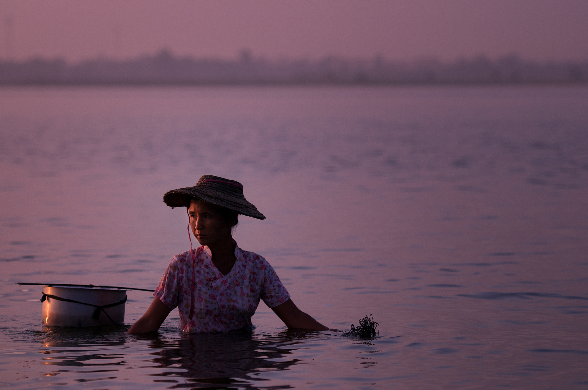 A woman  fishes with a net in the shallow waters of Taungthaman Lake.