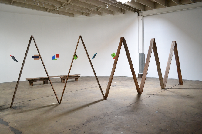 """installation view of """"Lean, 2"""", wooden sculpture in the foreground. Tempera and gouache paintings on a curved wall behind the sculpture.    2011"""