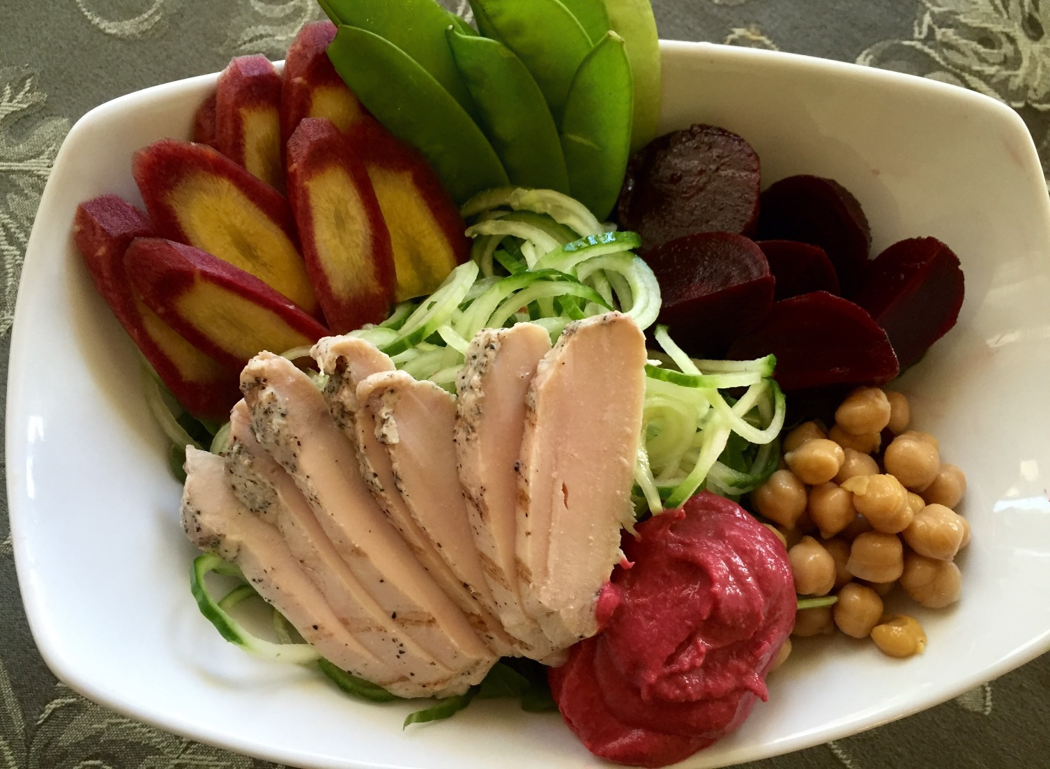 Sliced Grilled Chicken Breast over Spiralized Cucumber, Rainbow Carrots, Chickpeas, Snap Peas, Beets and Beet Hummus
